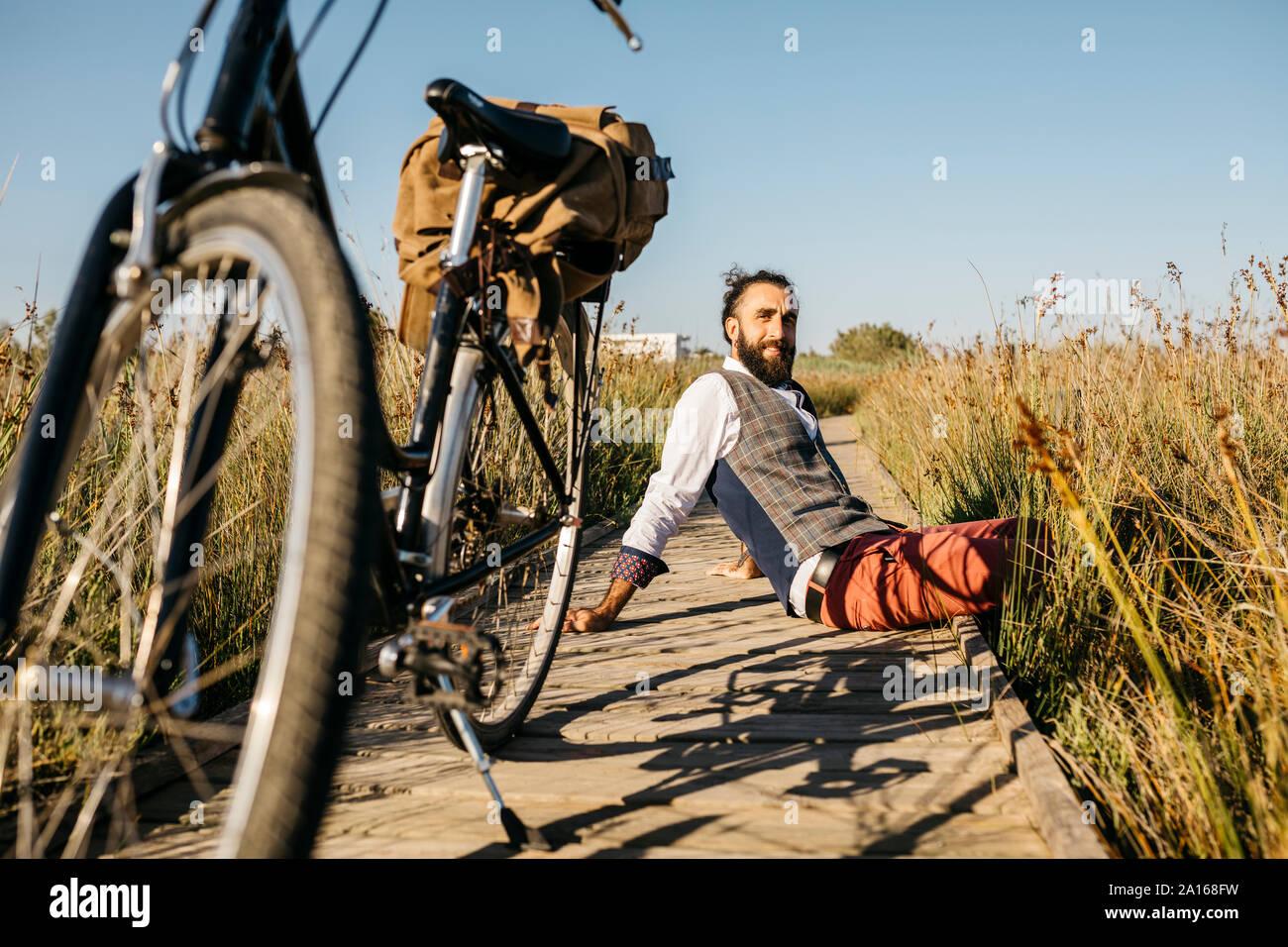 Ben vestito uomo seduto su una passerella di legno in campagna accanto a una bicicletta Foto Stock