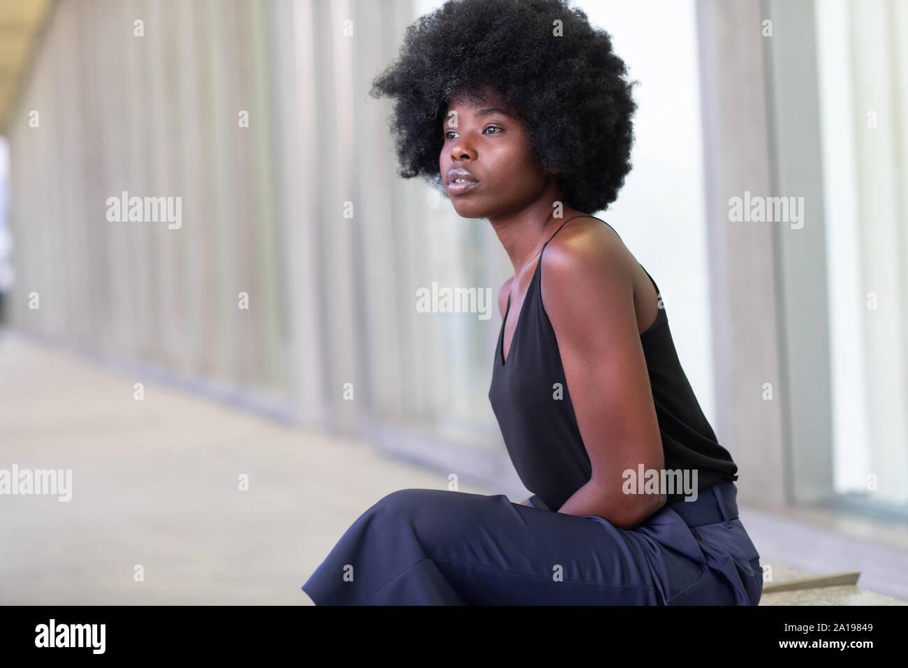 Piuttosto giovane donna africana su strade cittadine, seduta sul banco di lavoro Foto Stock
