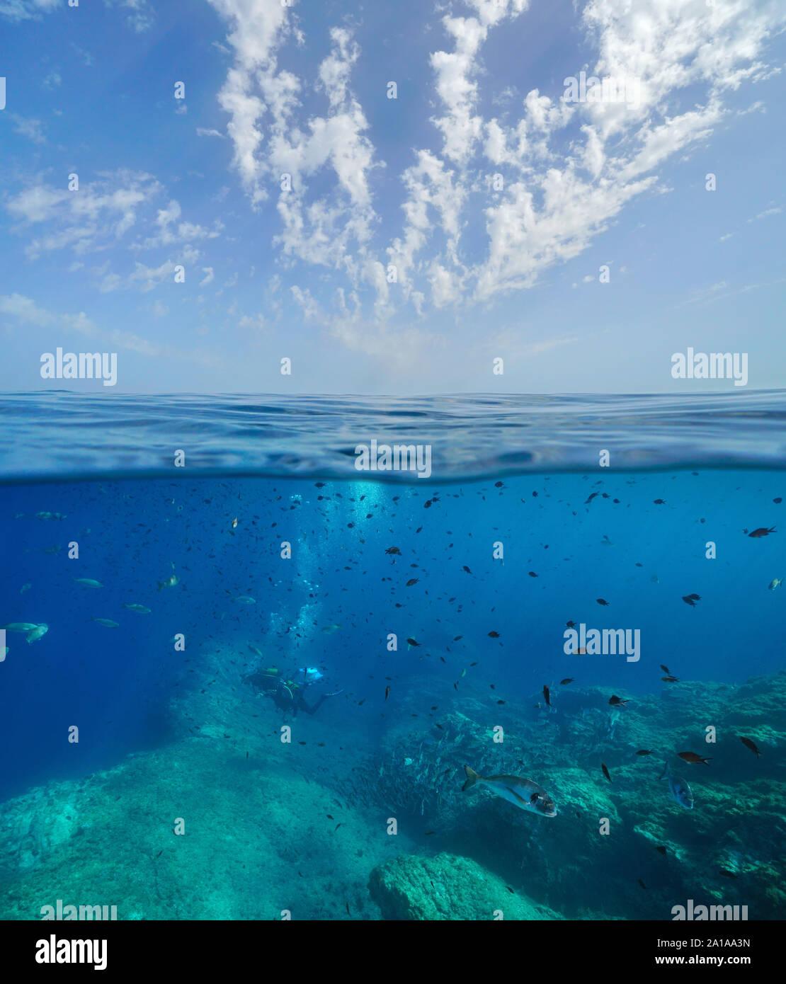 Paesaggio marino del Mar Mediterraneo, molti pesci con subacquei sott'acqua e cielo blu con nuvole, vista suddivisa al di sopra e al di sotto della superficie dell'acqua, Francia Foto Stock