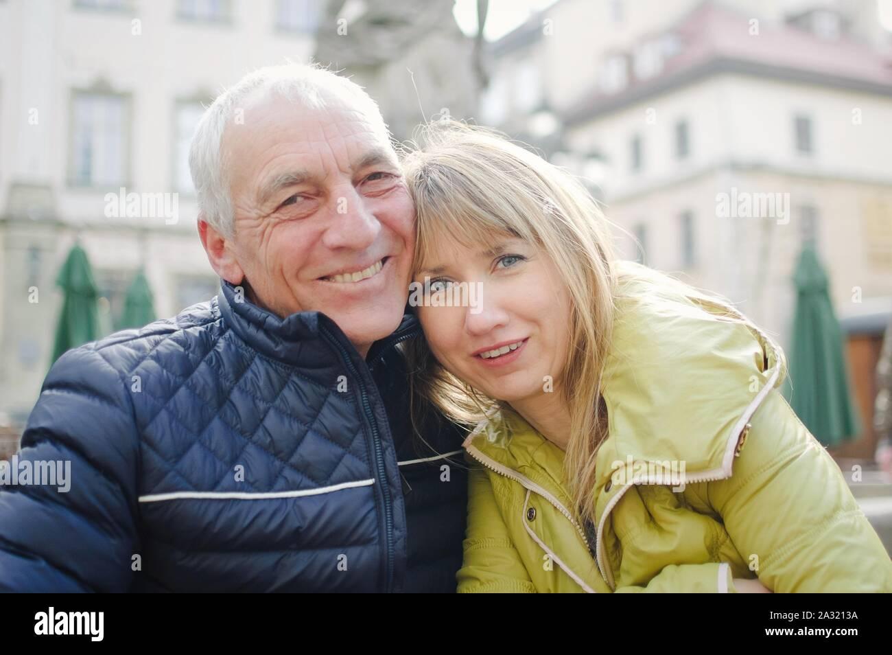 Bel uomo anziano è abbracciando la sua giovane moglie bionda di trascorrere del tempo insieme all'aperto nella città antica in primavera o in autunno. Foto Stock
