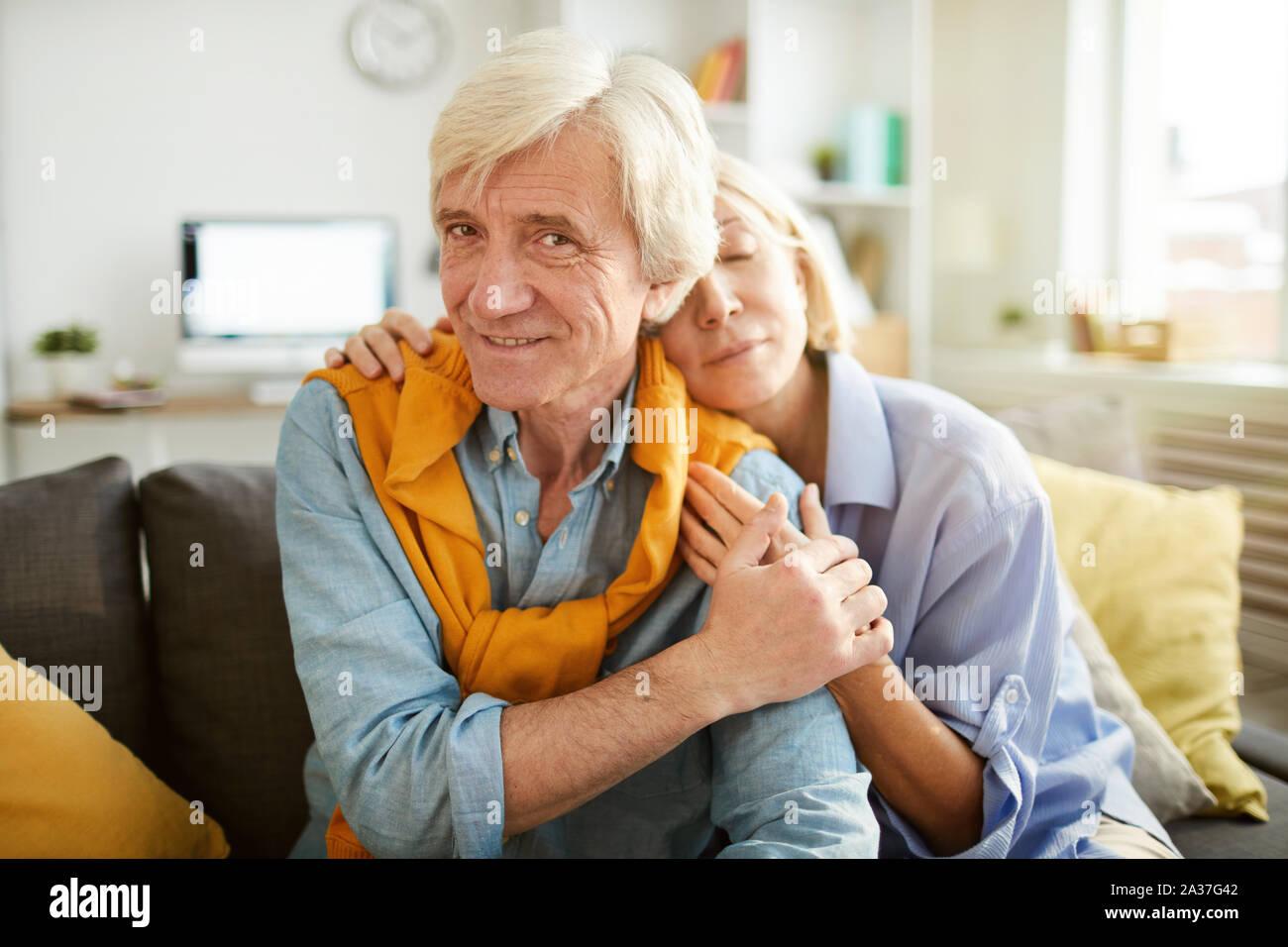 Ritratto di amorevole coppia senior abbracciando seduti sul comodo divano di casa, spazio di copia Foto Stock