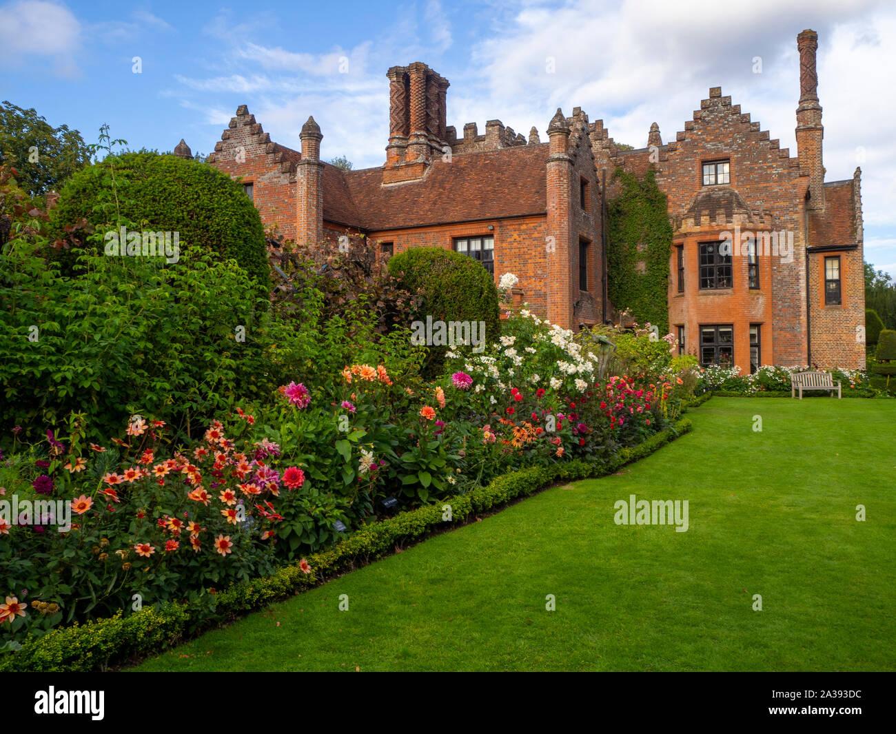 Verso sud confini dello stabilimento, Chenies Manor House e giardino in una bella serata ai primi di settembre.Prato, dalie, arbusti, dotate di architettura di Tudor. Foto Stock