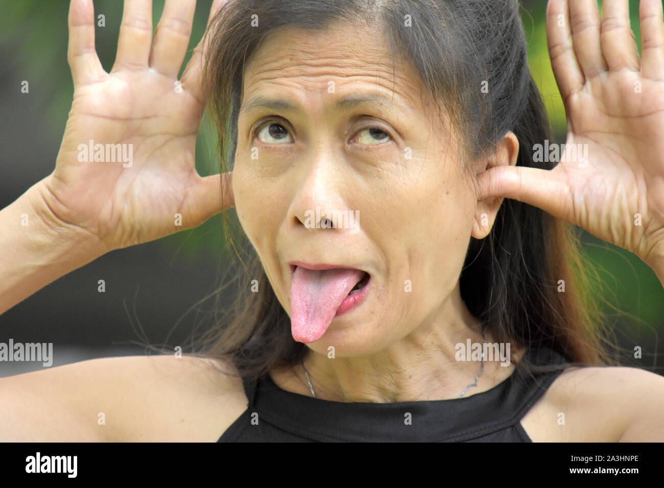 Una femmina Senior facendo facce buffe Foto Stock