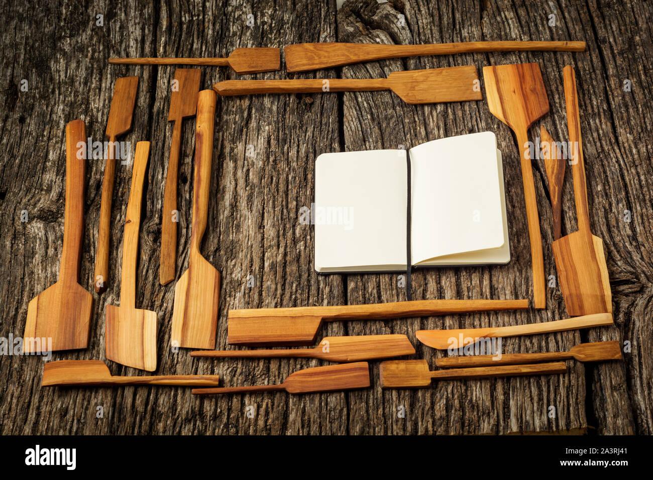 Cornice fatta di utensili da cucina in un casale rustico tavolo da cucina con notebook. Foto Stock