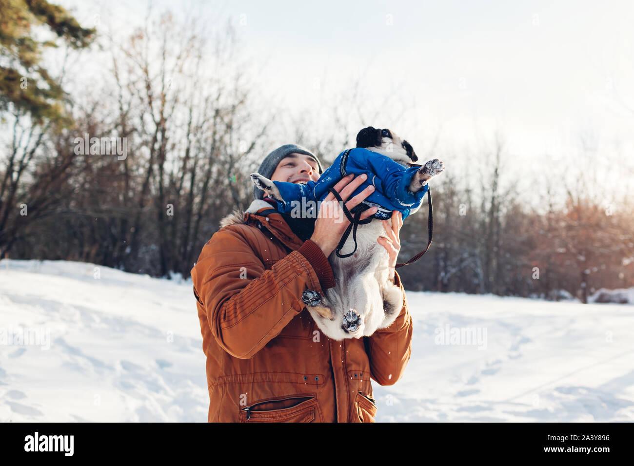 Pug dog camminando con il suo padrone. L'uomo gioca con il suo pet e divertirsi. Cucciolo indossando cappotto invernale Foto Stock