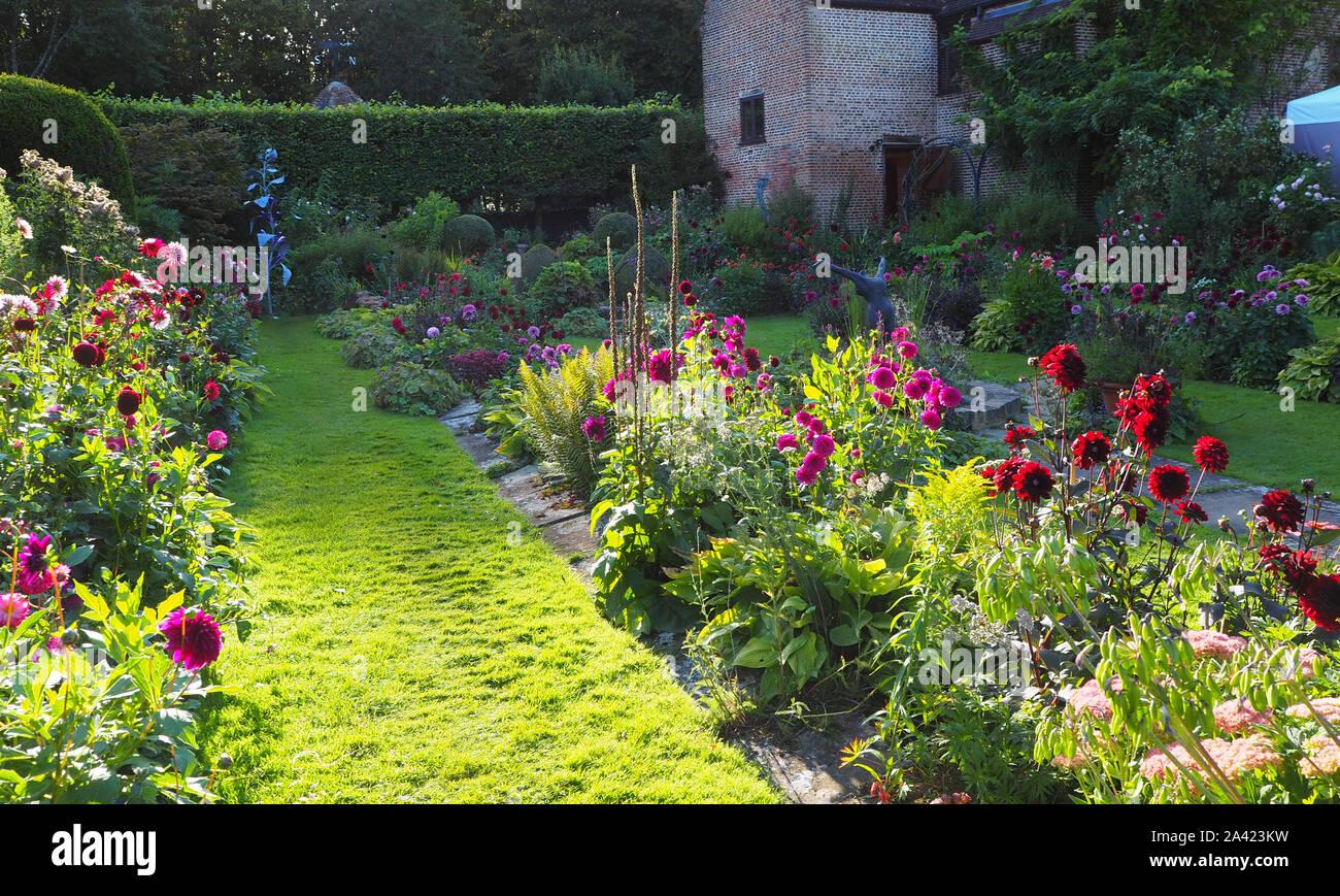 Il Sunken garden a Chenies, Buckinghamshire su una soleggiata sera nel settembre;il restaurato Pavilion.Colorata varietà dahlia e luminoso percorso erboso. Foto Stock