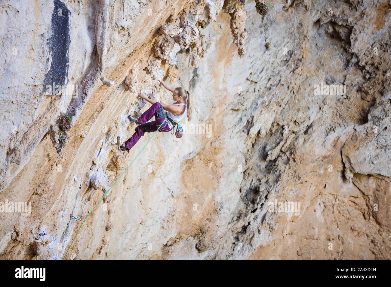 Giovani caucasici donna climbing impegnativo percorso sulla rupe a strapiombo Foto Stock