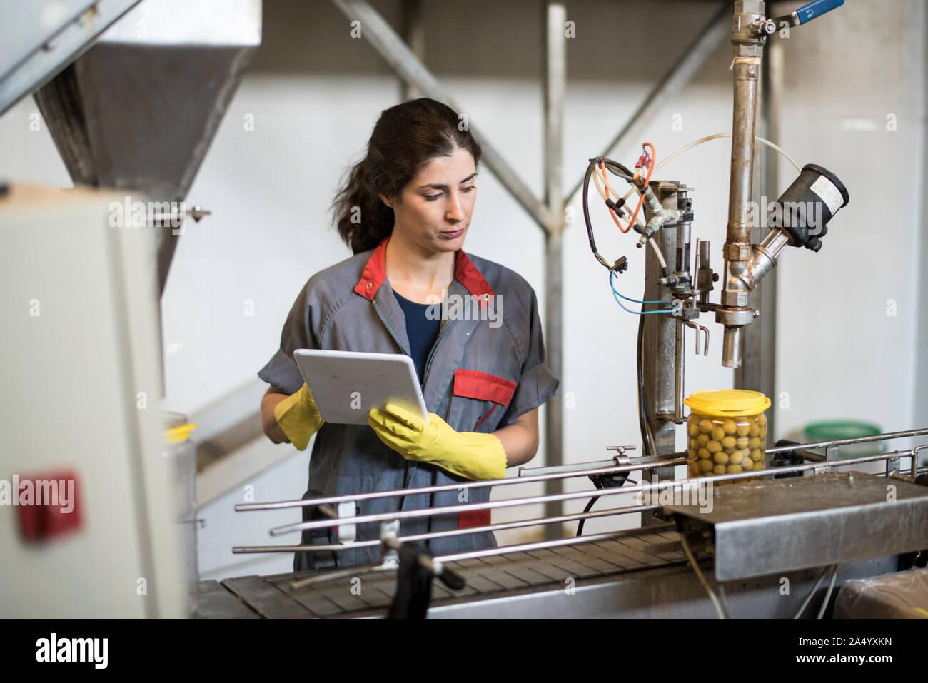 Lavoratore donna con tablet rivedere il nastro trasportatore macchina in stabilimento alimentare Foto Stock