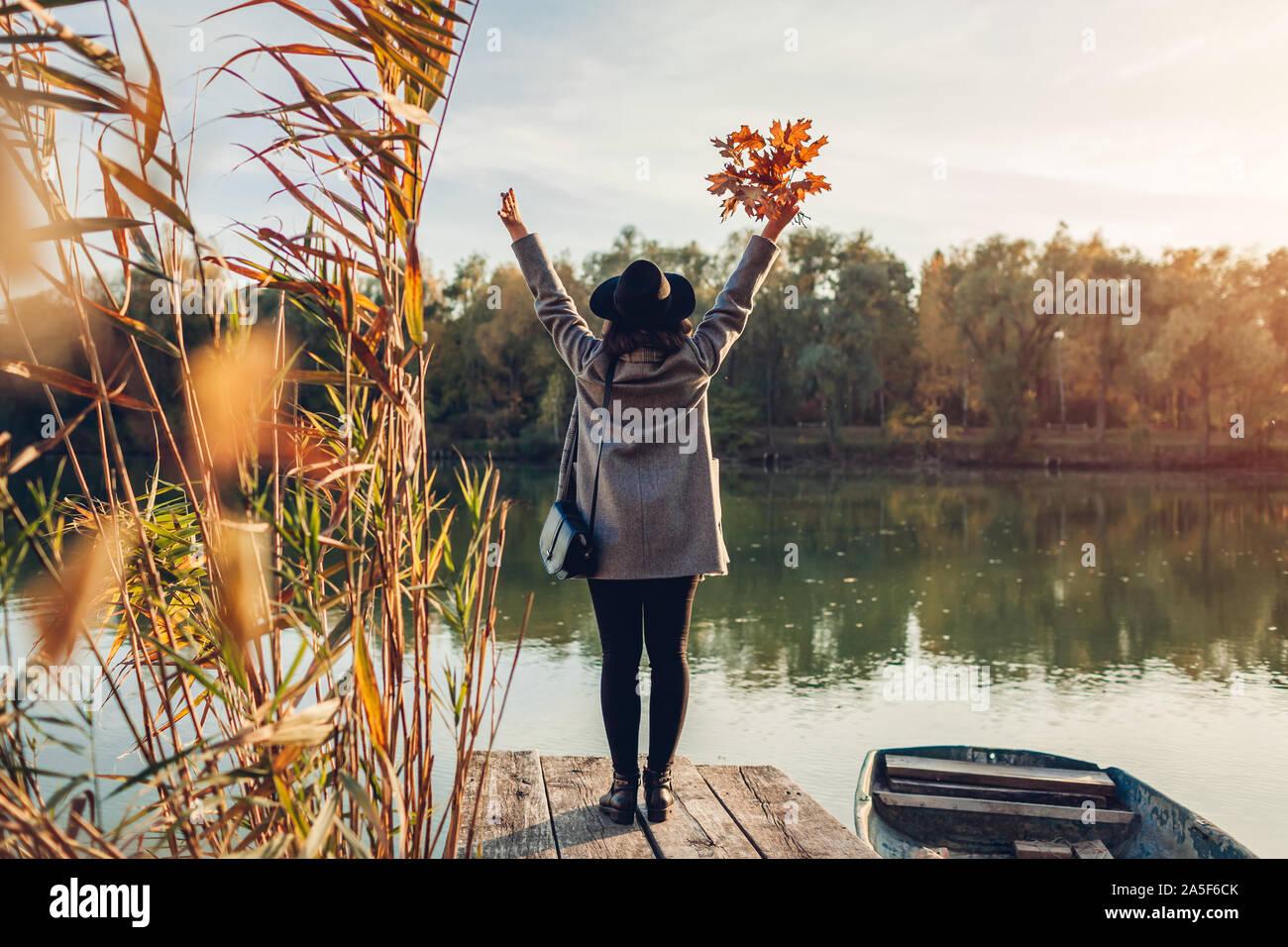 Donna felice camminando sul molo sul lago in barca alzando le mani e ammirando il paesaggio autunnale. Caduta stagione attività Foto Stock