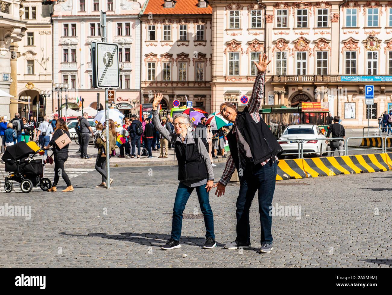 Coppia senior gesticolando e gesti sul marciapiede, Piazza della Città Vecchia di Praga, Repubblica Ceca Foto Stock