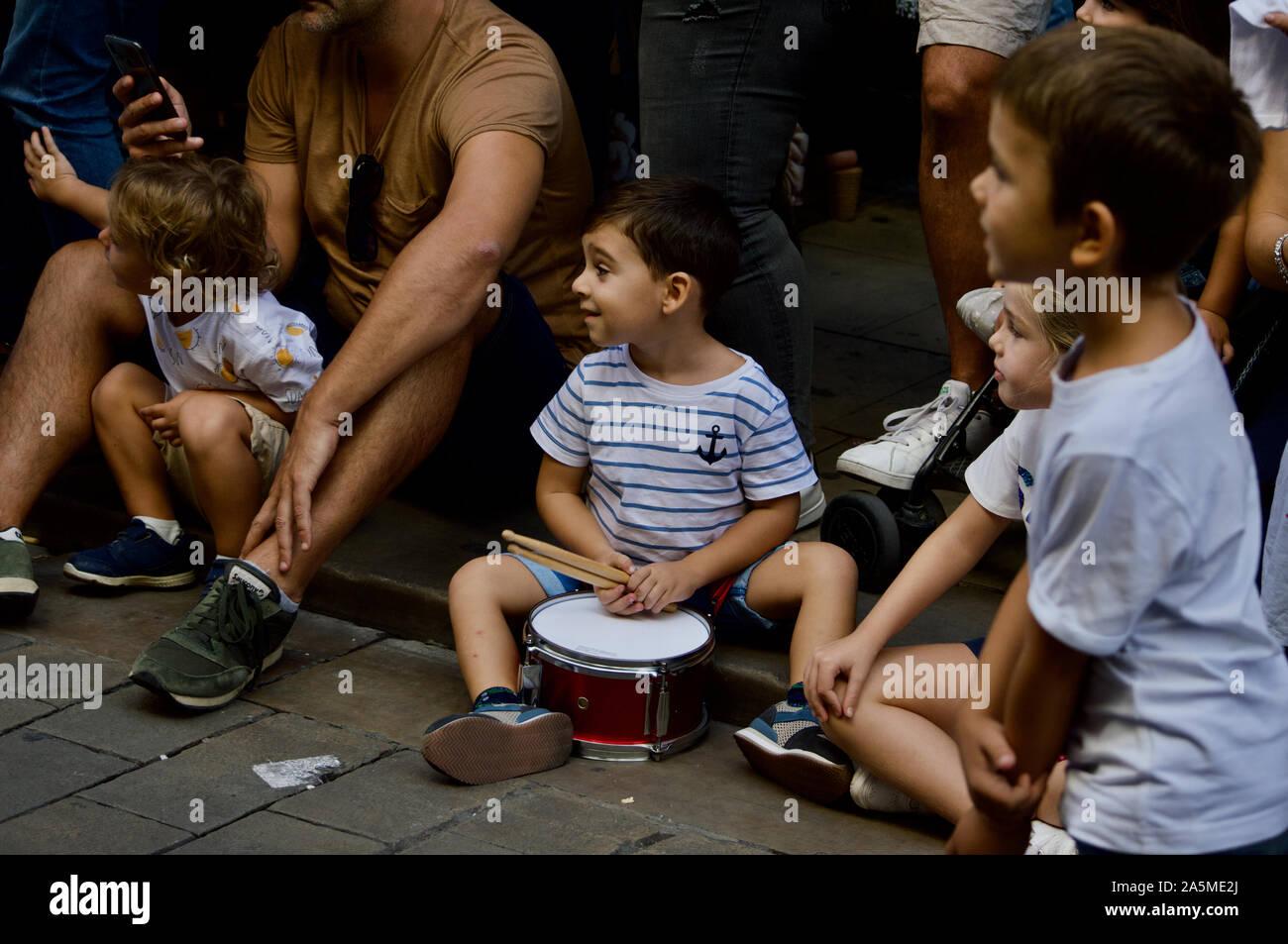 Un ragazzo giocando un tamburo presso la parata dei giganti durante la Merce Festival 2019 a Placa de Sant Jaume a Barcellona, Spagna Foto Stock