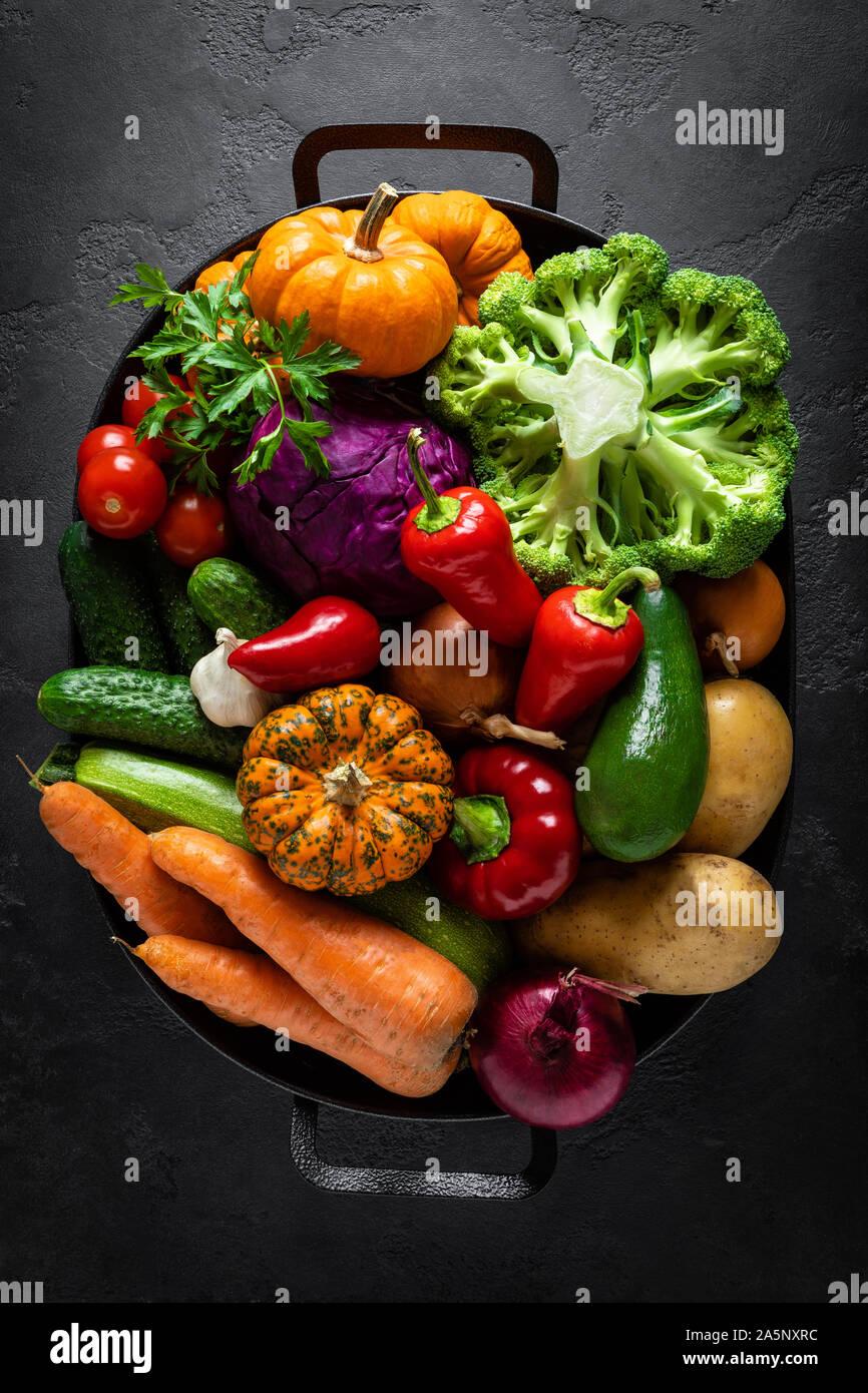 Sfondo culinario con fresche verdure crude su un nero tavolo da cucina, sana alimentazione vegetariana concetto, piatto composizione laici, vista dall'alto Foto Stock