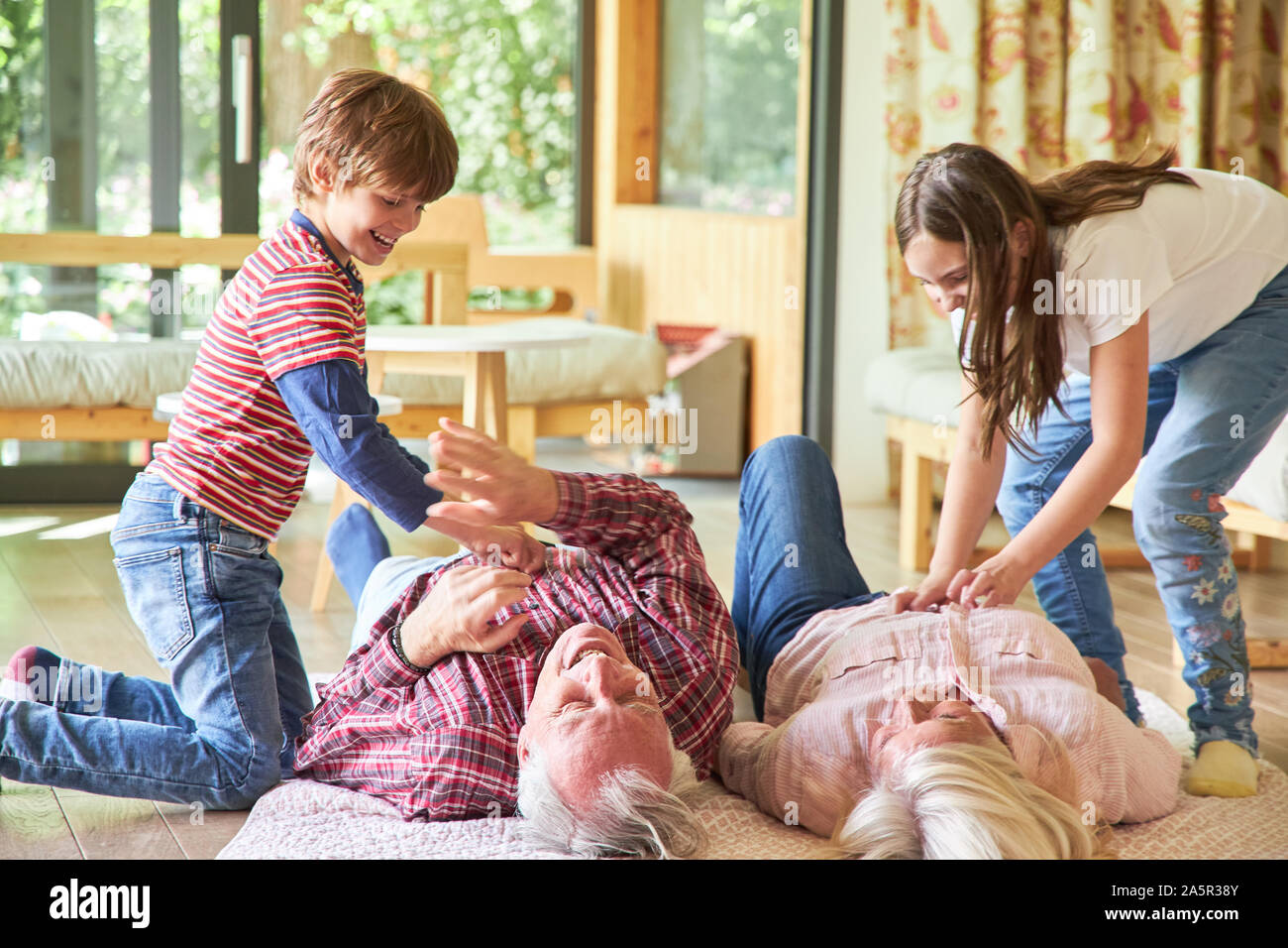 Nonni sul pavimento sono tickled dai propri nipoti Foto Stock