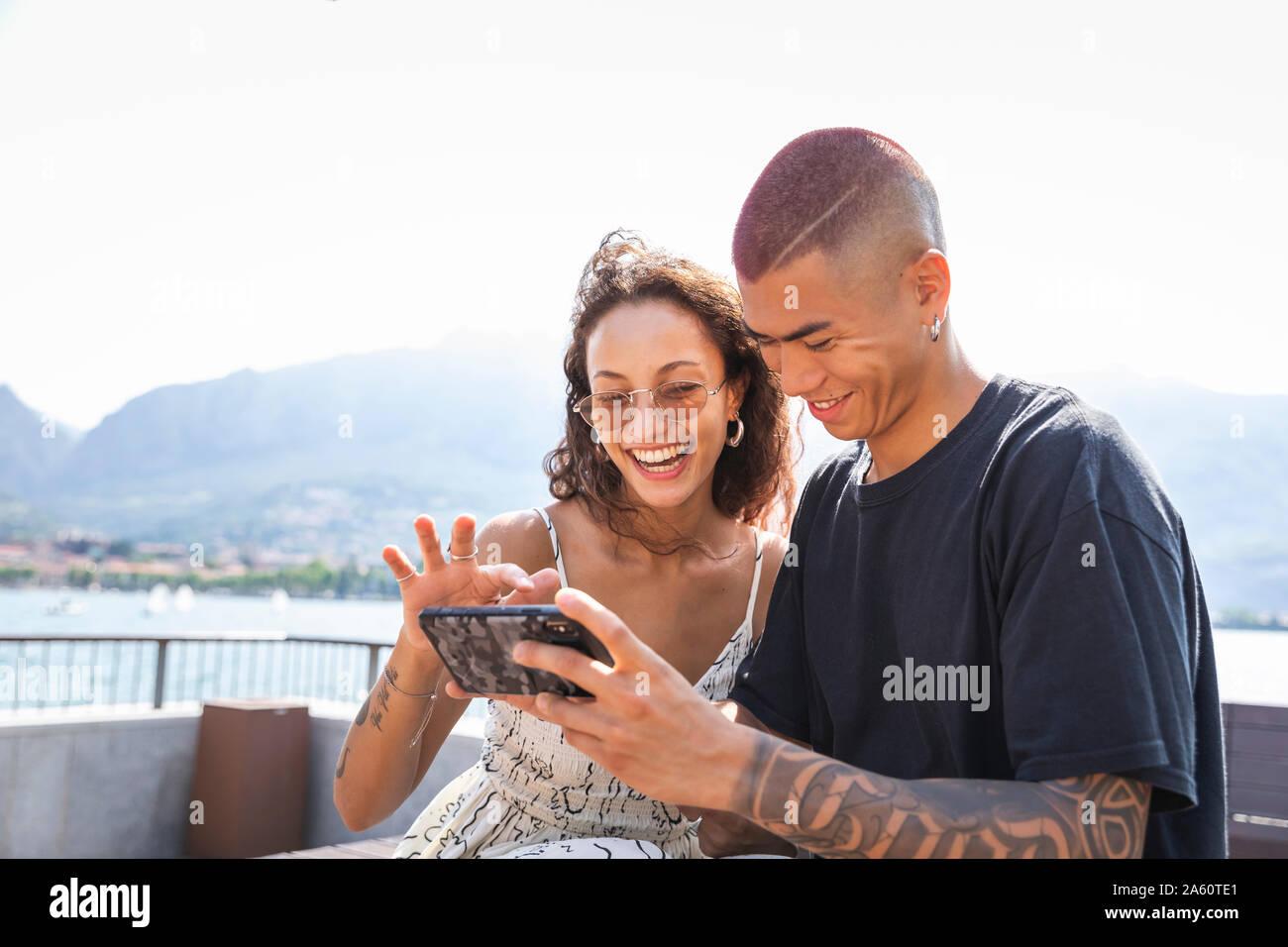 Felice coppia giovane guardando al telefono cellulare, Lecco, Italia Foto Stock