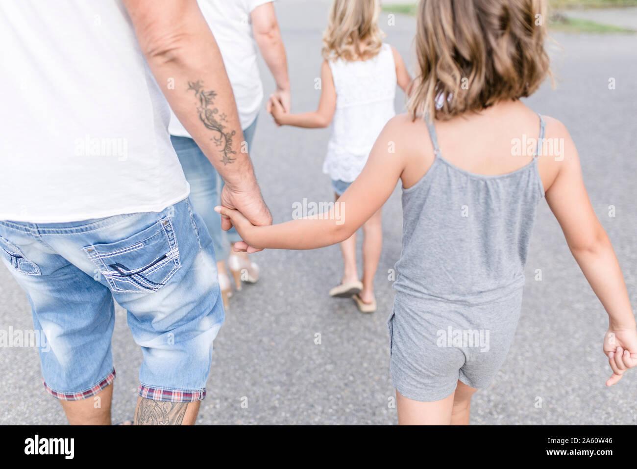 Vista posteriore della famiglia camminando mano nella mano su una strada Foto Stock