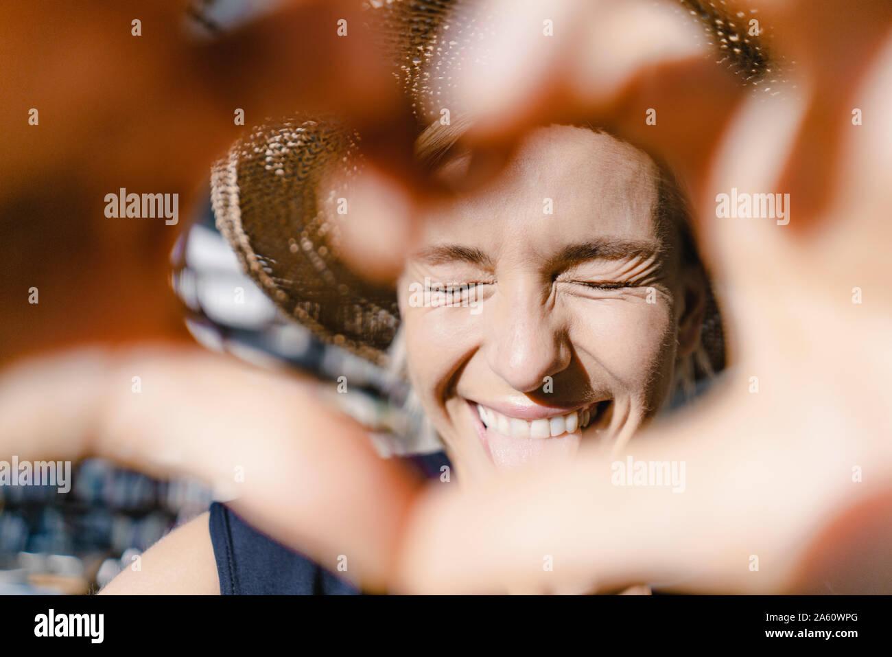 Donna con cappello di paglia, guardando verso il sole, rendendo a forma di cuore telaio del dito Foto Stock