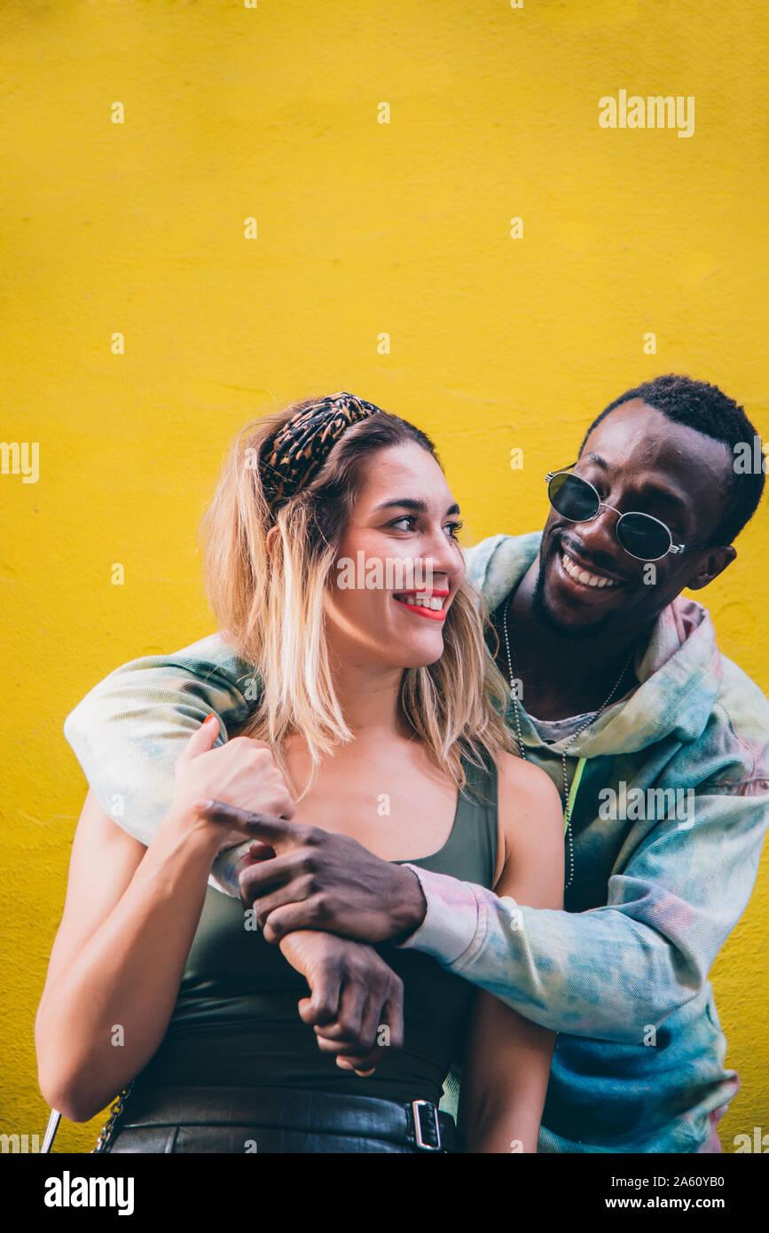 Ritratto di coppia felice nella parte anteriore della parete gialla Foto Stock