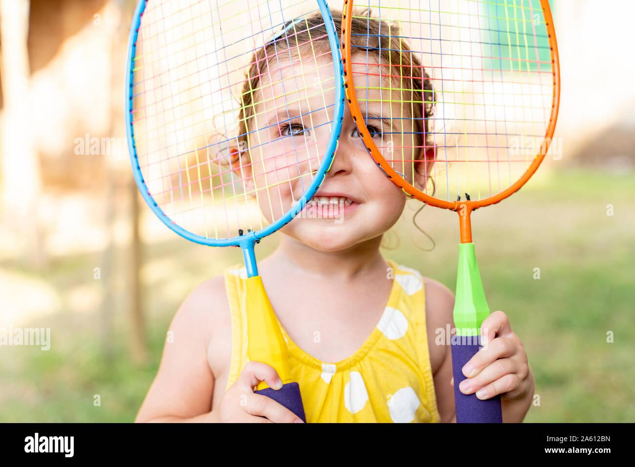 Bambina giocando con colorati badminton racchette all'aperto in estate Foto Stock