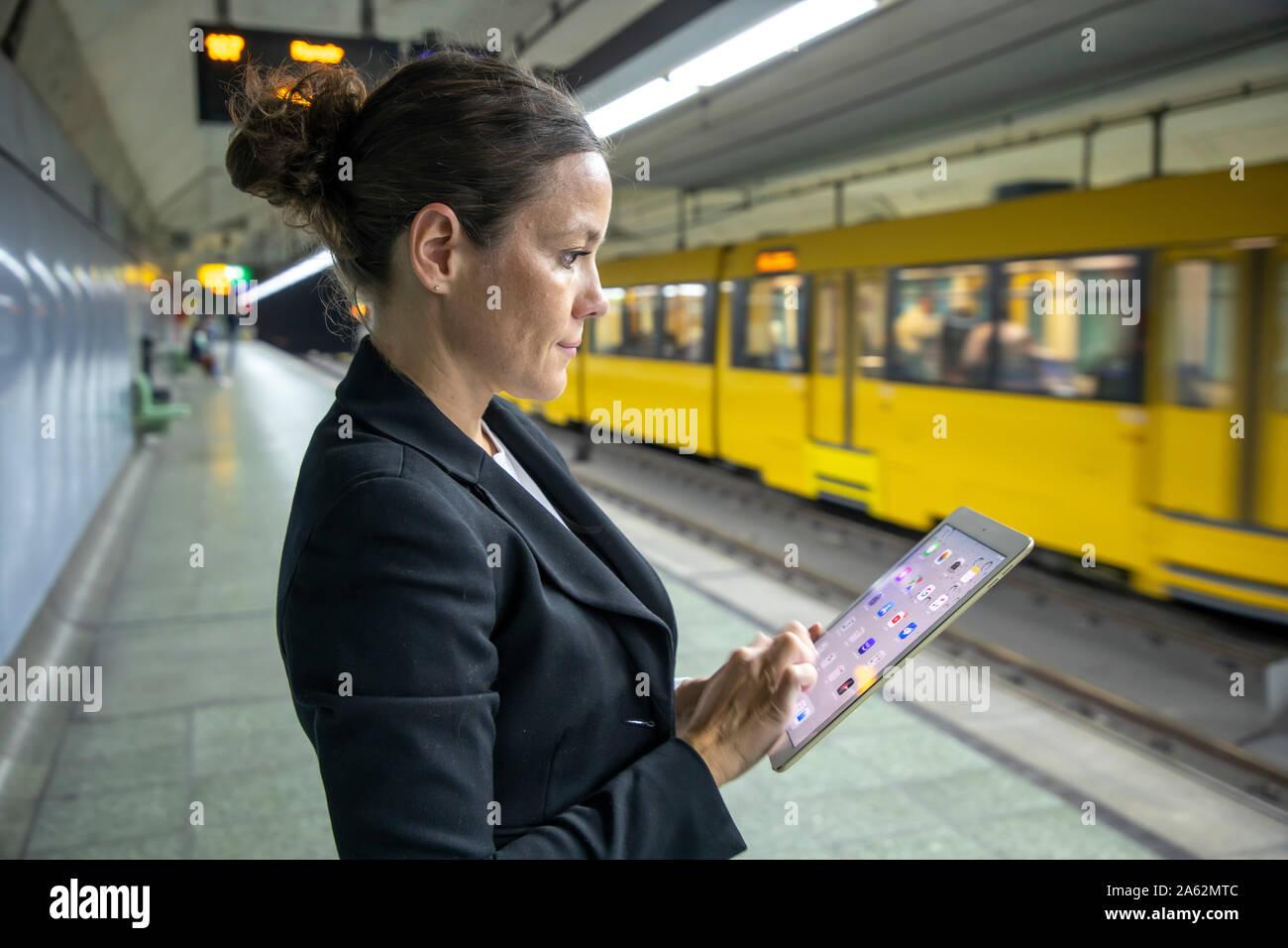 Una donna che lavora fino, dalla strada al lavoro, sulla strada, mobile, stazione metropolitana, Foto Stock