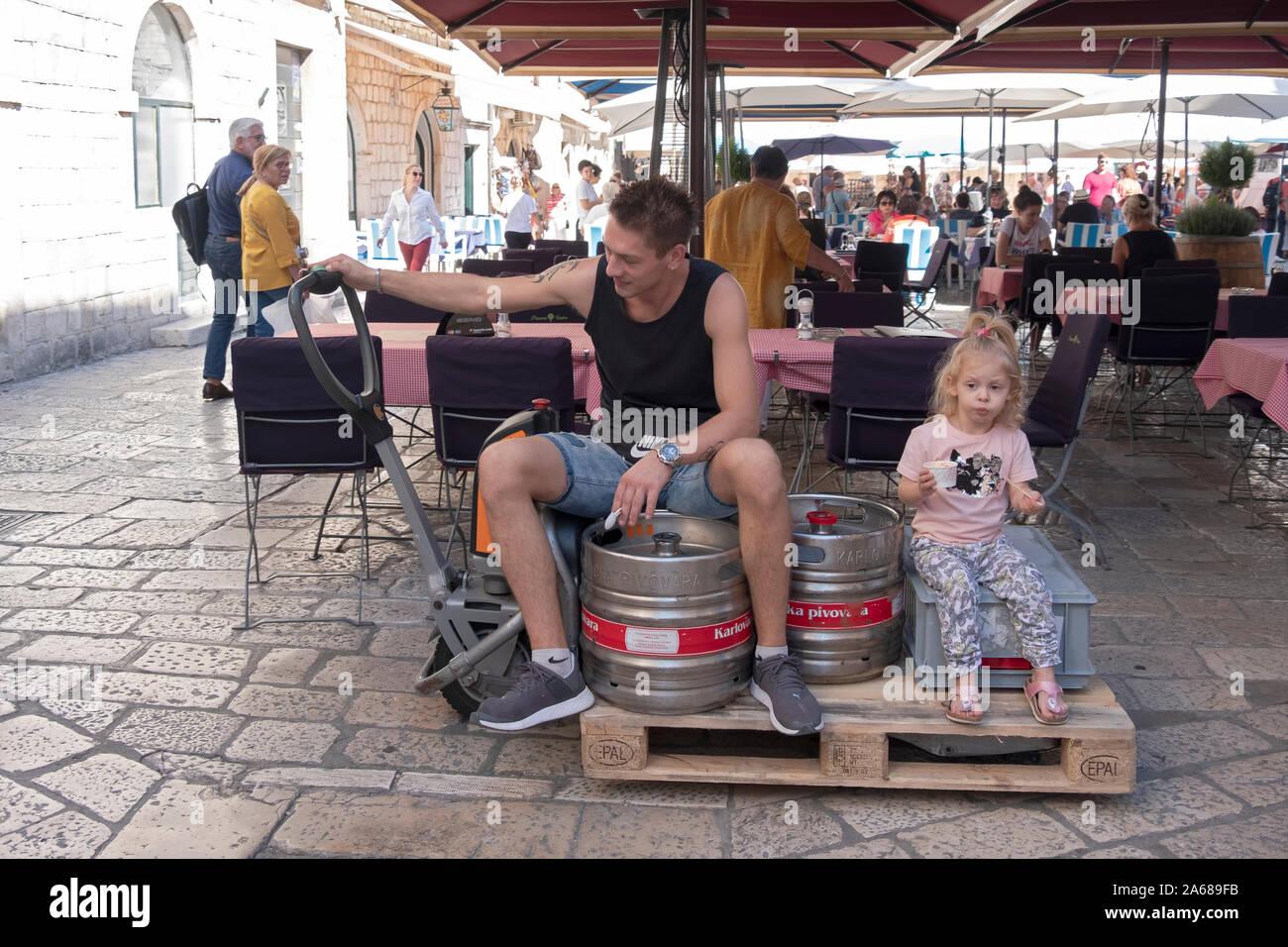 Un padre e sua figlia ride su un sollevatore motorizzato nella città vecchia sezione di Dubrovnik, Croazia. Foto Stock