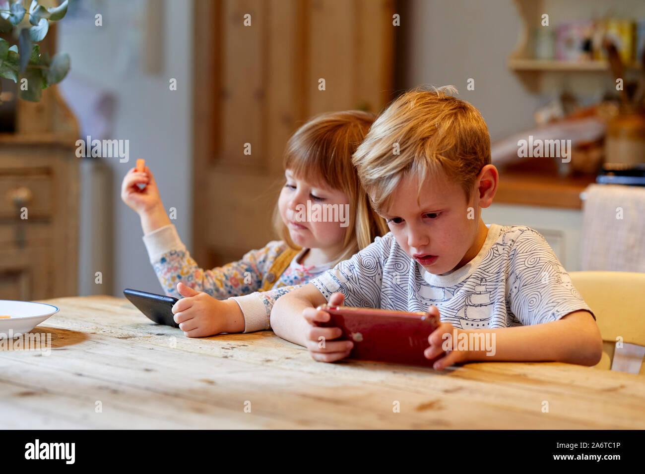 Bambini che giocano sui dispositivi Foto Stock