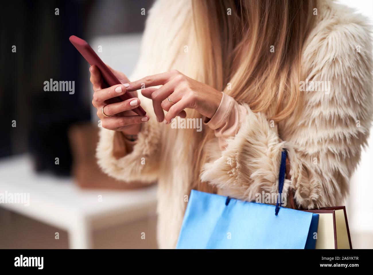 Le donne in età adulta shopping per i vestiti in boutique in autunno e utilizza lo smartphone Foto Stock