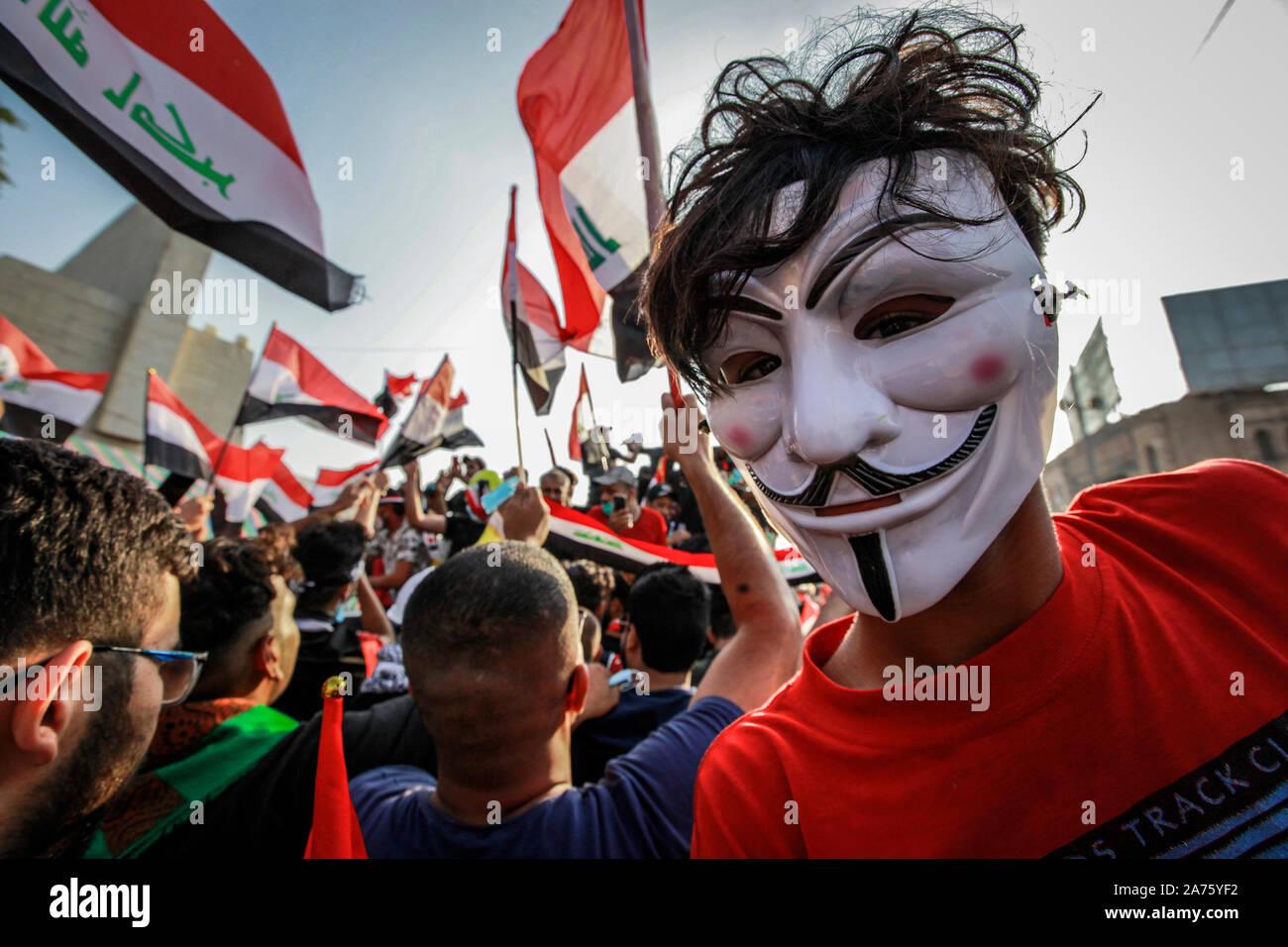 Baghdad in Iraq. 30 ott 2019. Un iracheno chi indossa la maschera di Guy Fawkes unisce persone sventolare la bandiera irachena durante un governo anti-dimostrazione a Piazza Liberazione. Manifestanti iracheni il mercoledì ha respinto le dichiarazioni di leader di al Parlamento il principale rivale di blocchi di lavorare insieme per rovesciare il governo attuale in un tentativo di placare questo mese di disordini, e hanno ribadito le loro richieste, comprese la cacciata del parlamento, elezioni anticipate e riforme legislative e costituzionali. Credito: Ameer Al Mohammedaw/dpa/Alamy Live News Foto Stock