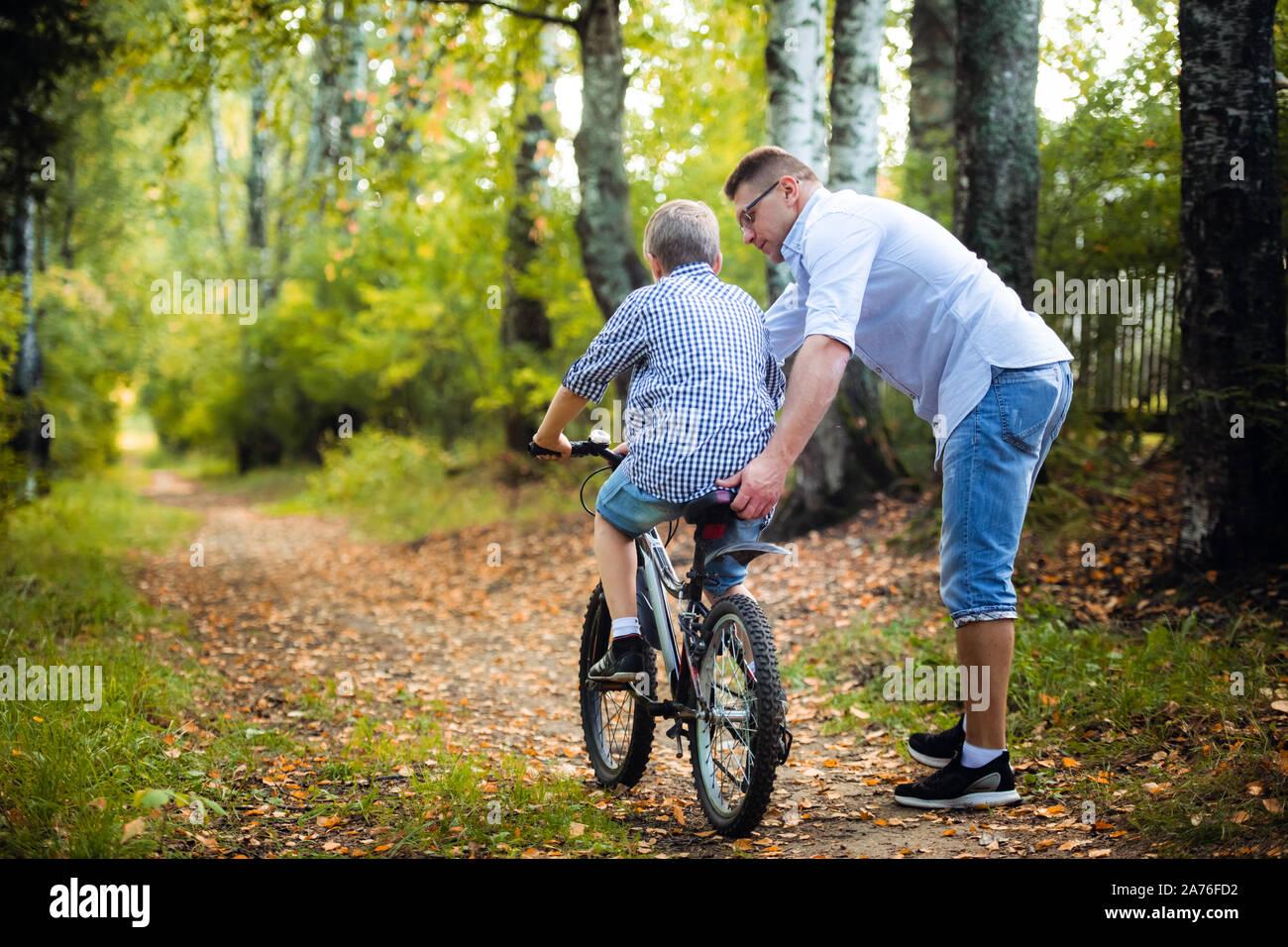 Giovane padre insegnando il suo figlio ad andare in bicicletta Foto Stock