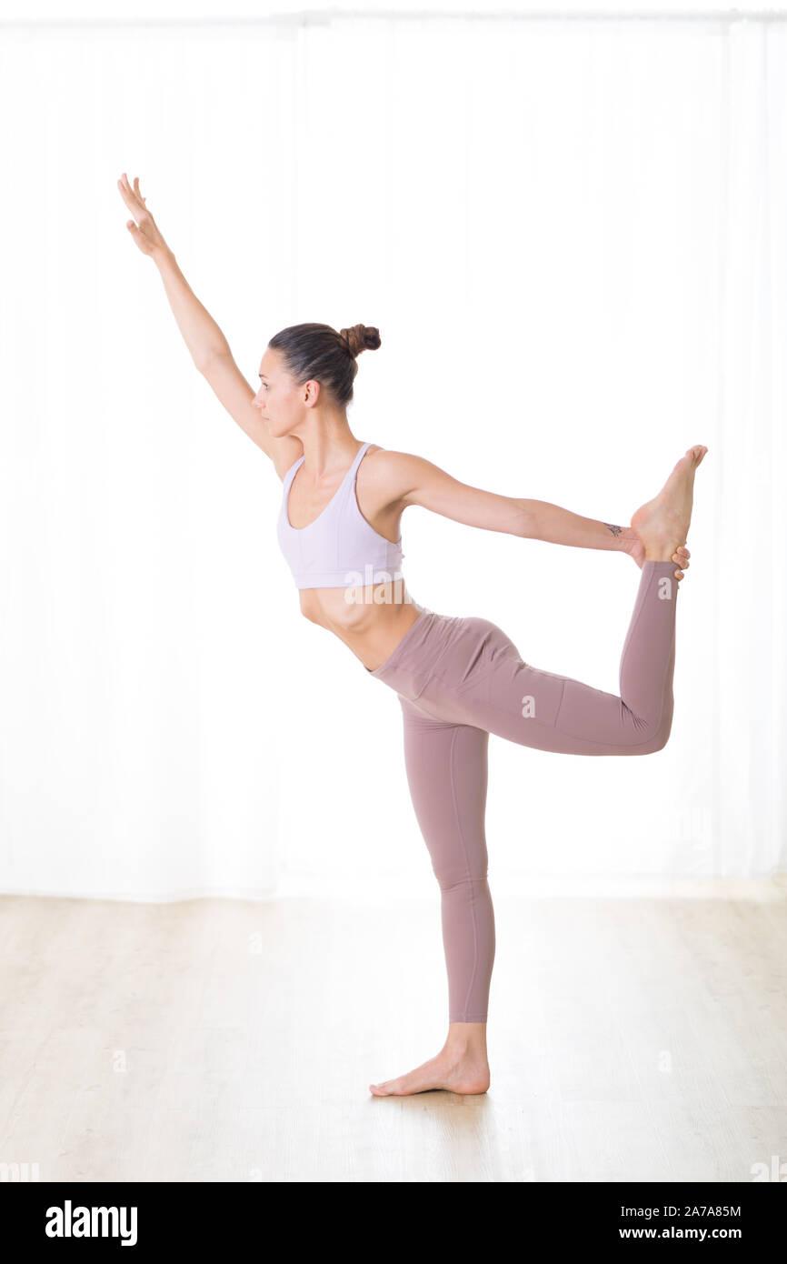 Ritratto di splendida sportiva attiva giovane donna a praticare yoga in studio. Bella ragazza pratica Dandayamana Dhanurasana, prua permanente tirando pongono Foto Stock
