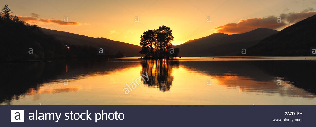 Il sole che tramonta dietro un'isola di alberi da Loch Tay da Perth and Kinross, Scozia. Foto Stock