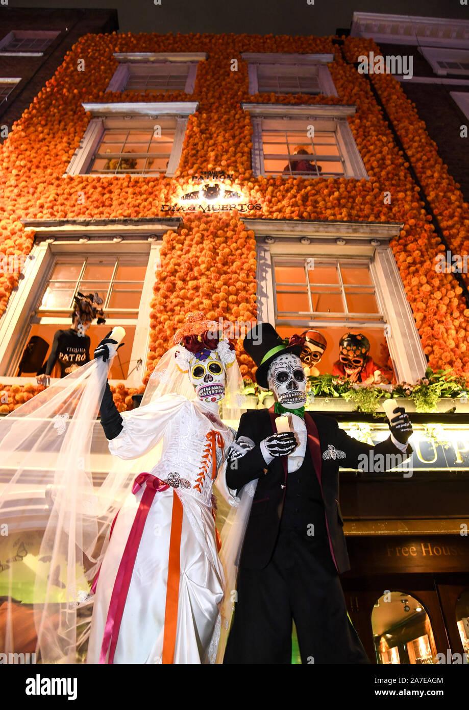 Solo uso editoriale tradizionale messicano Dia de Muertos caratteri come la Calavera Catrina, farfalle monarca e zucchero teschi, festeggiano per le strade di Soho il Patron Tequila il Giorno dei Morti celebrazioni, Londra. Foto Stock