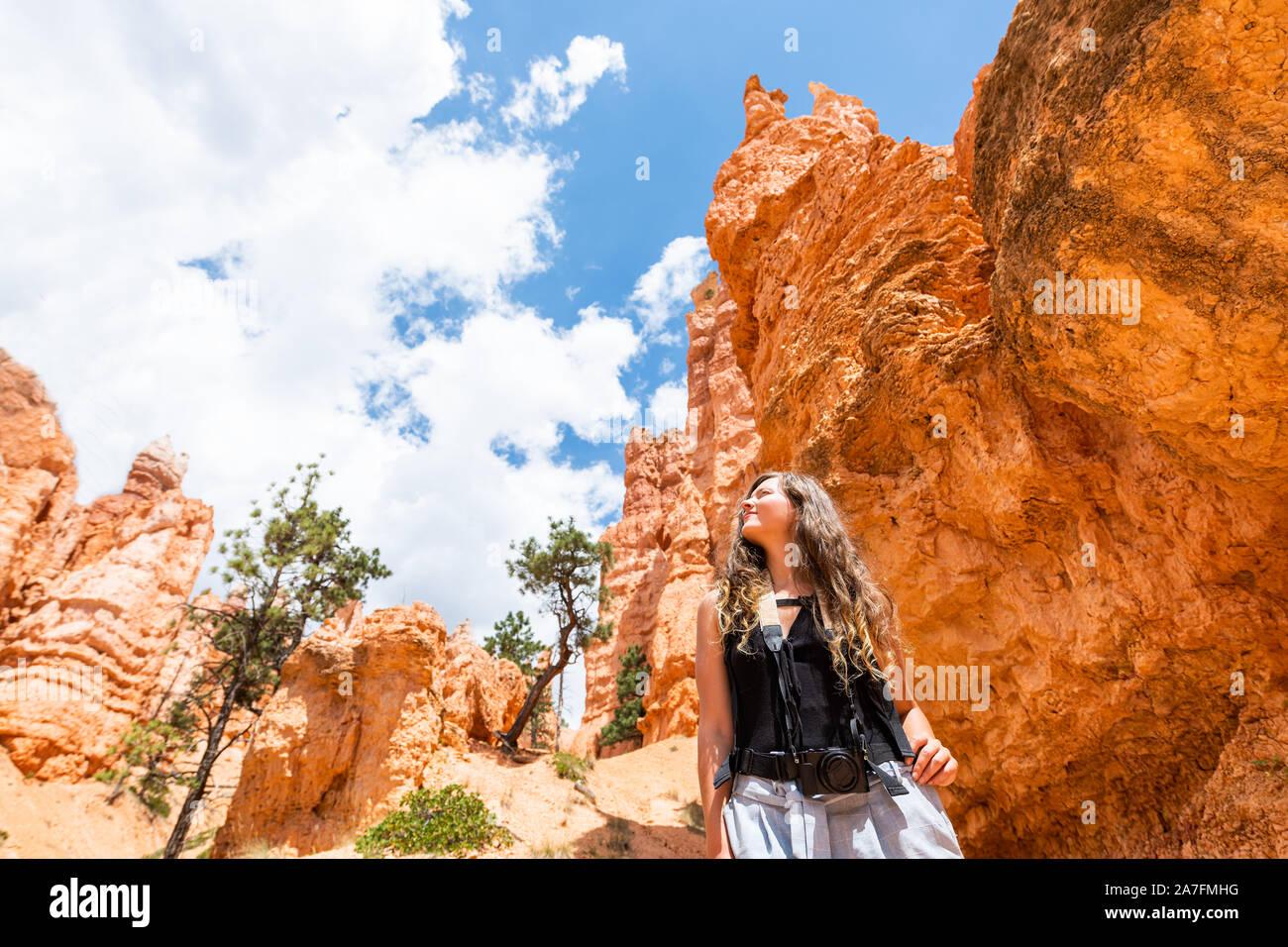 Giovane donna in piedi guardando il paesaggio del deserto vista estiva nel Parco Nazionale di Bryce Canyon su loop Navajo ampio angolo con la fotocamera e il cielo Foto Stock