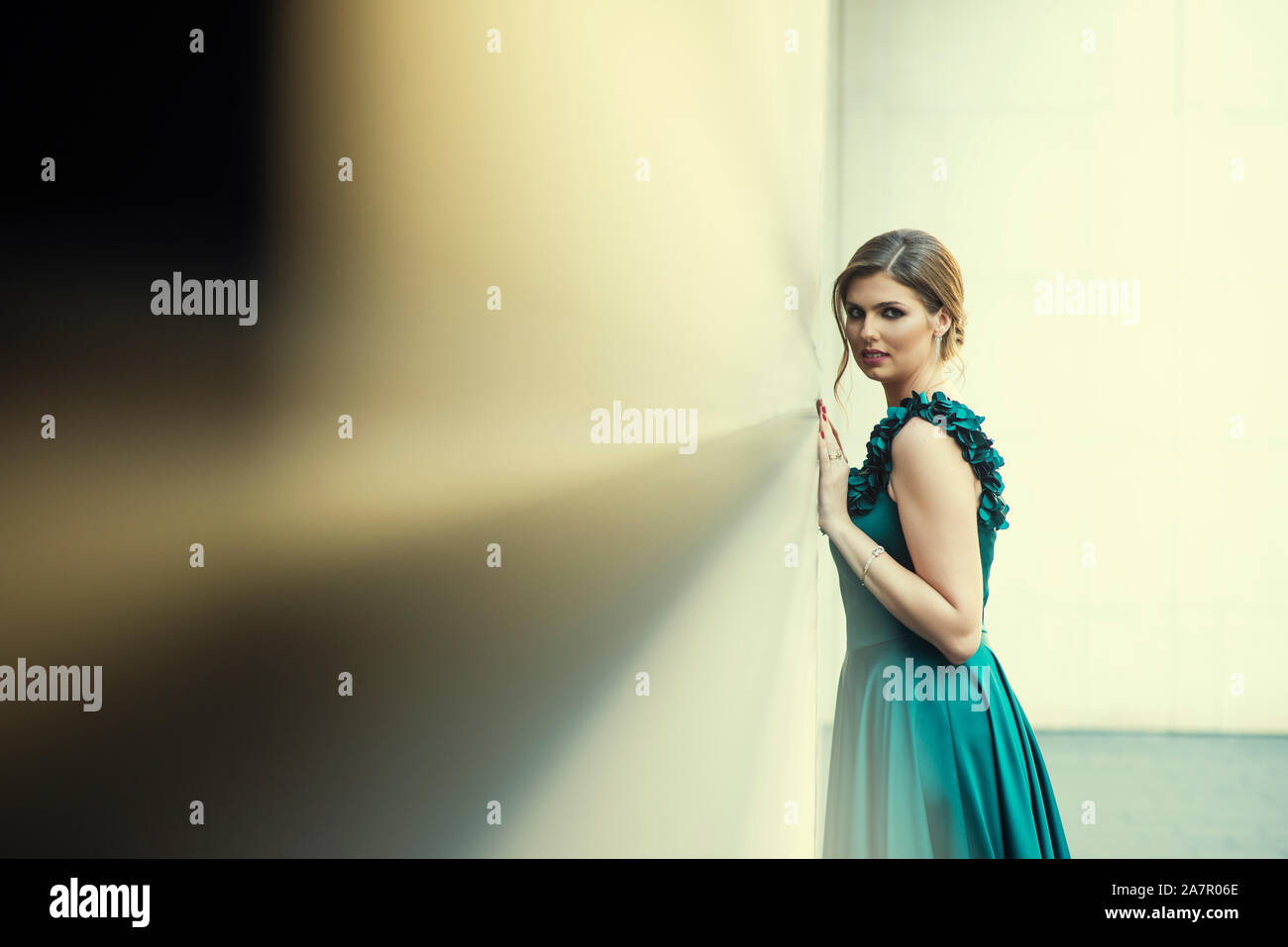 Bella donna appoggiata contro la parete all'esterno guardando la fotocamera Foto Stock