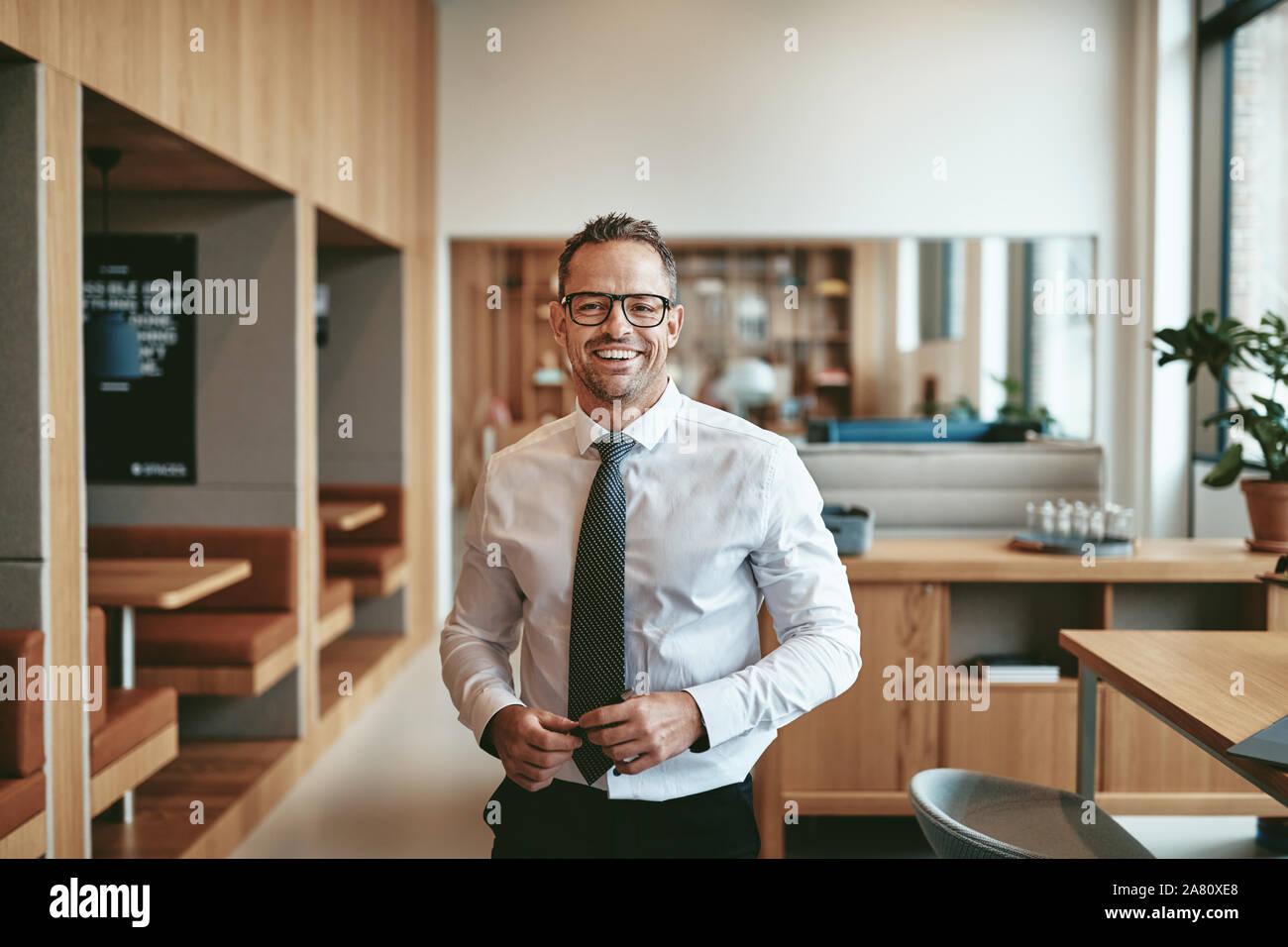 Imprenditore matura sorridente con fiducia mentre sta in piedi da solo nel bar di un luminoso ufficio moderrn Foto Stock