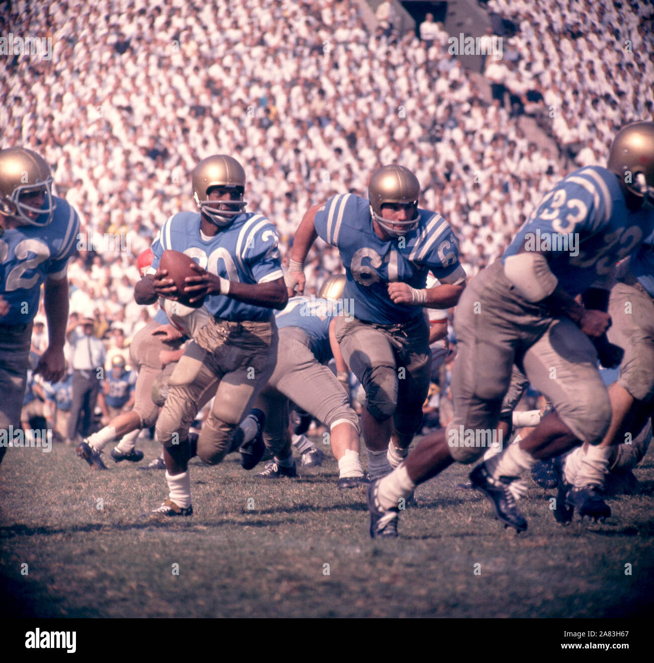 LOS ANGELES, CA - 6 ottobre: Singleton Ezell #20 del UCLA Bruins corre con la palla come il suo compagno di squadra Dave Stout #61 corre per blocco durante un gioco di NCAA contro la Ohio State Buckeyes il 6 ottobre 1962 presso il Los Angeles Memorial Coliseum di Los Angeles, California. (Foto di Hy Peskin) (numero impostato: X8760).Caption locale *** Ezell Singleton;Dave Stout Foto Stock