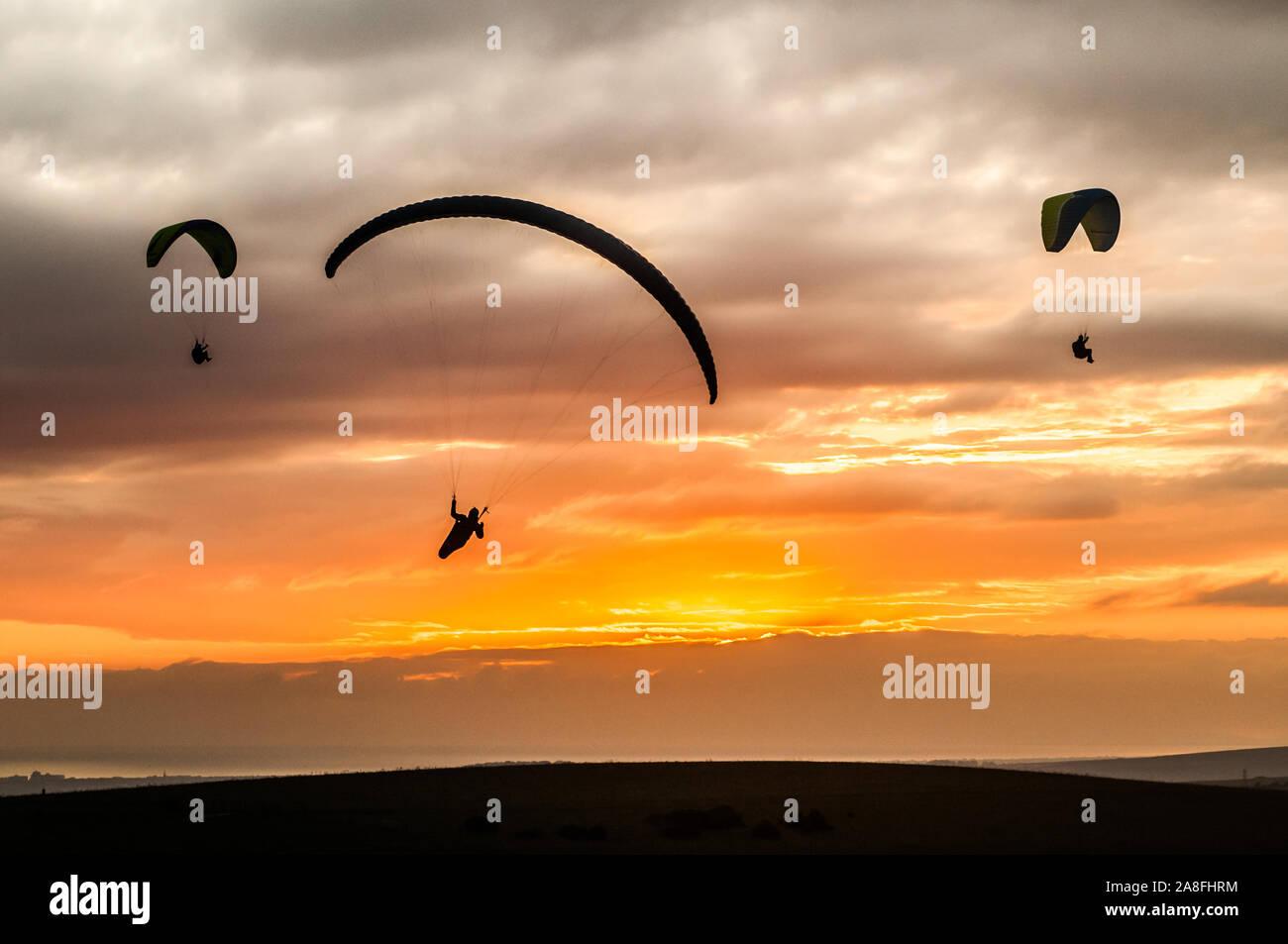 Diavoli Dyke, Brighton, East Sussex, UK..8th novembre 2019..Paragliders volare sulla fredda brezza Nord contro il sole e le nuvole sparse, sopra i Downs del sud, rende per scene mozzafiato. . Foto Stock