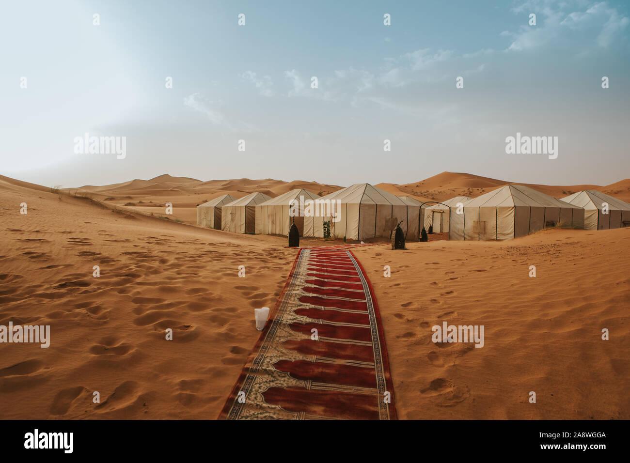 Splendido desert camp e tappeto sulla sabbia formando un corridoio con tende in background. Foto Stock