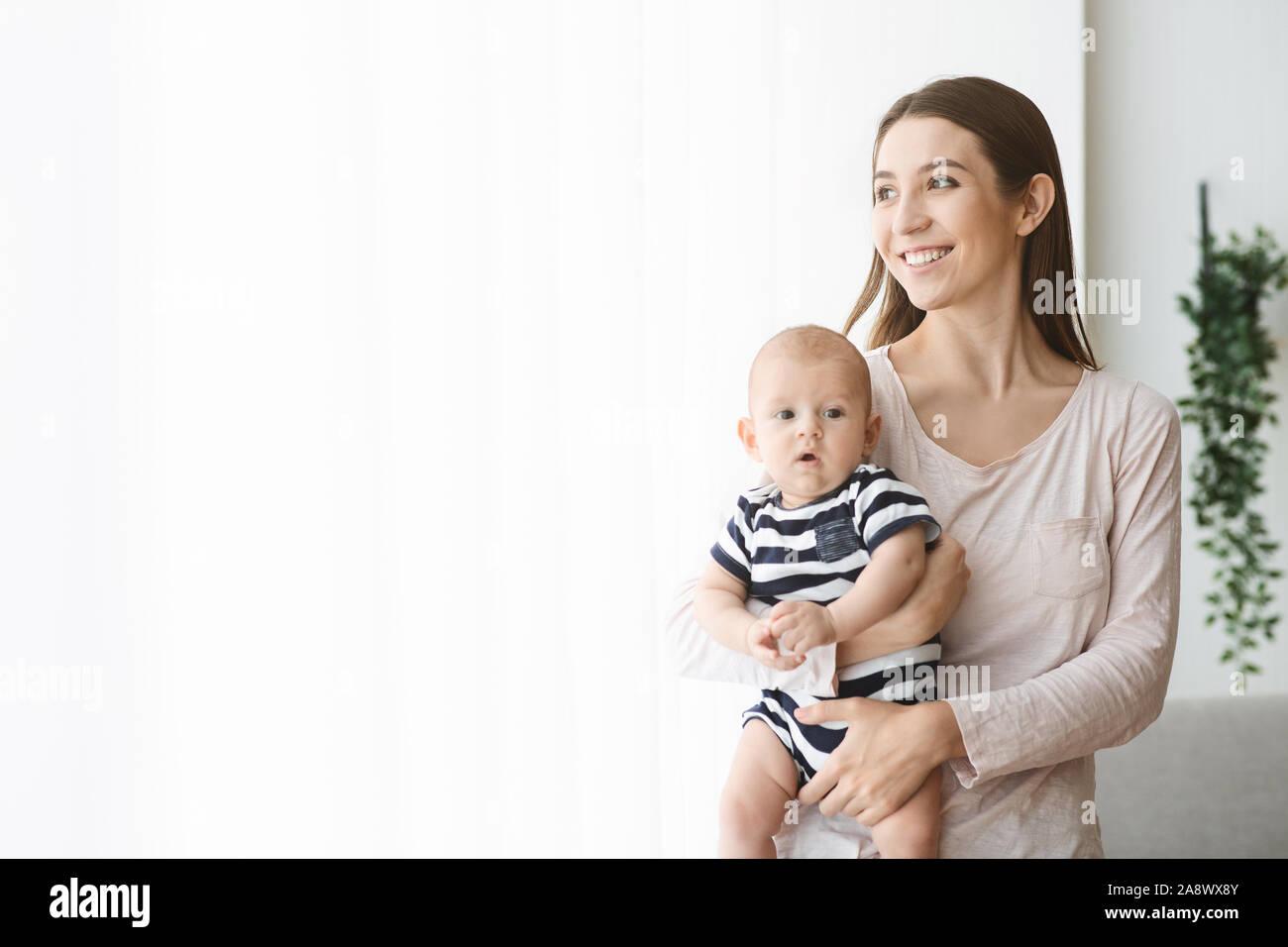 Felice azienda madre neonato e guardando fuori dalla finestra Foto Stock