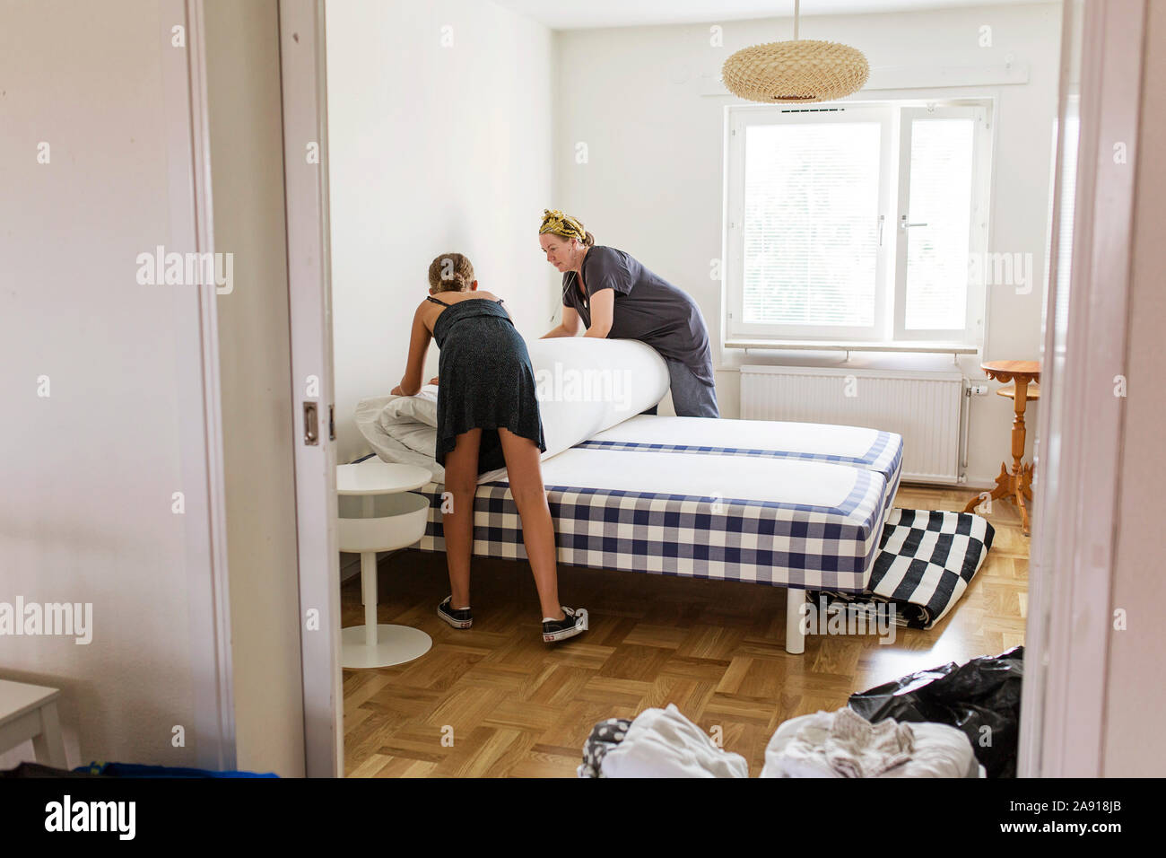 Madre e figlia rendendo letto Foto Stock