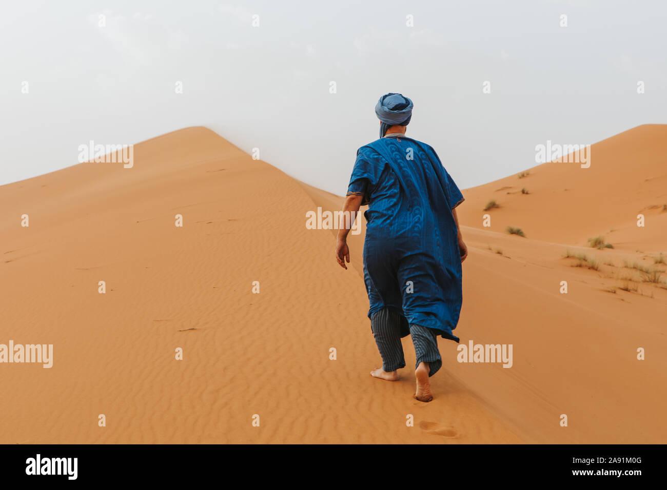 L'uomo con il classico riff vestiti a piedi dalle dune del deserto da soli. Foto Stock
