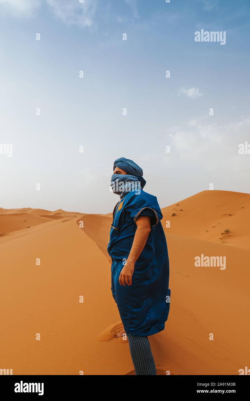 L'uomo con il classico riff vestiti in piedi sulle dune del deserto da soli. Foto Stock