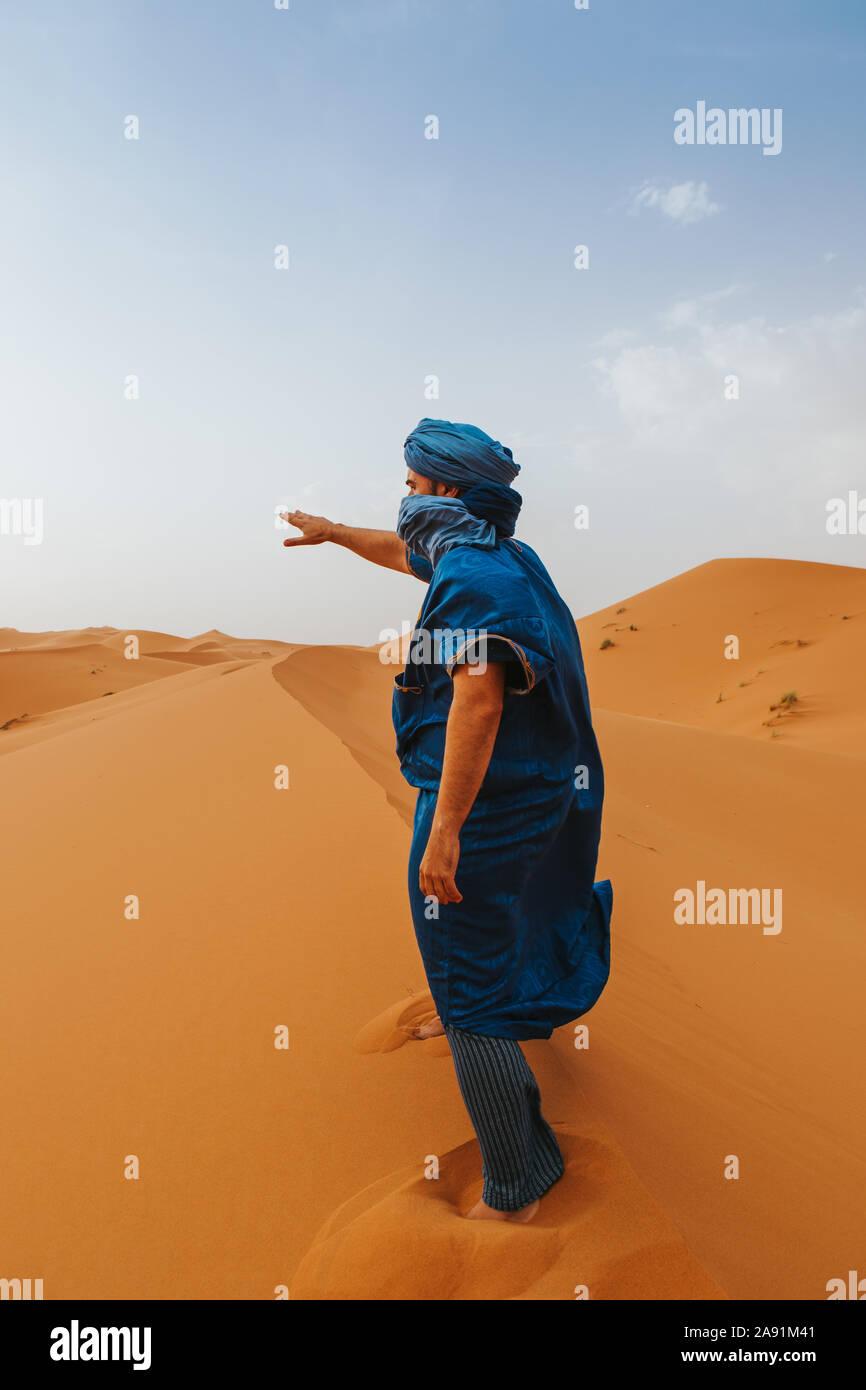 L'uomo con il classico riff vestiti in piedi e dispositivo di puntamento con la mano sulle dune del deserto da soli. Foto Stock