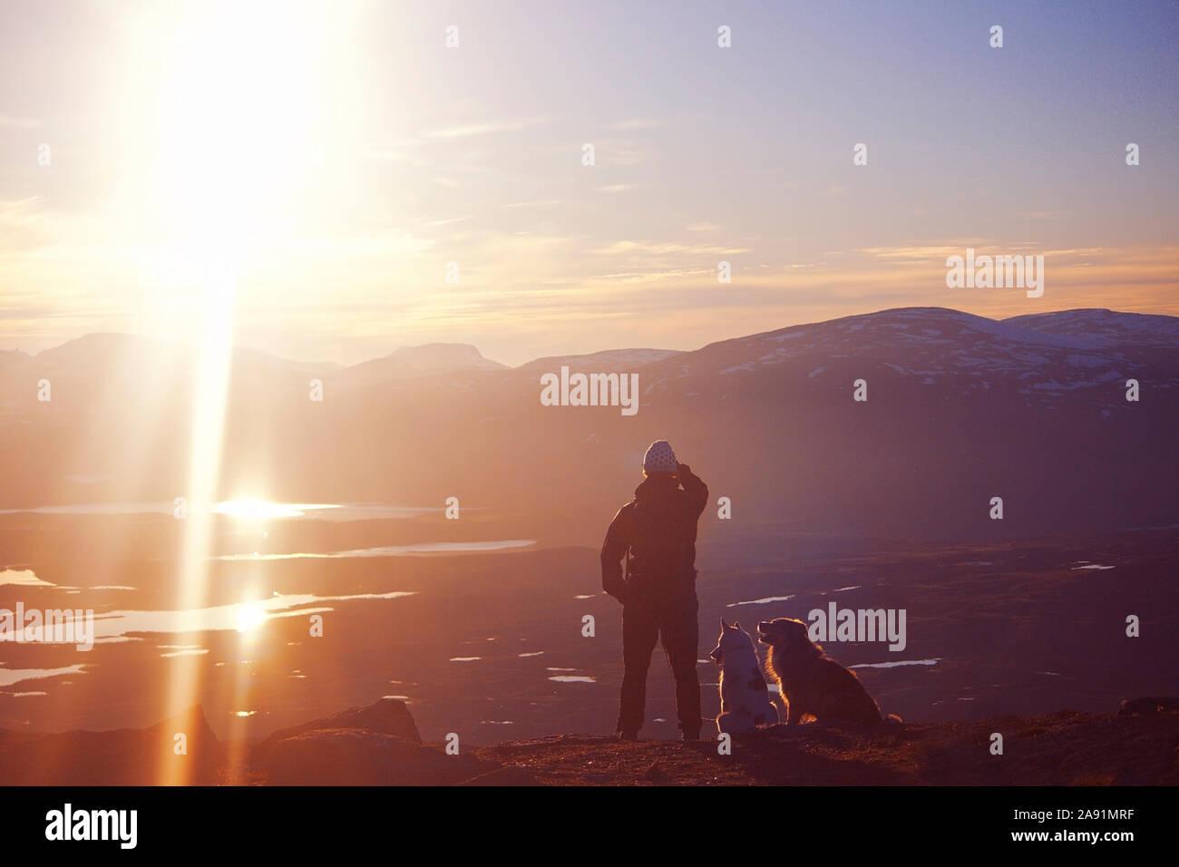 Persona con cani guardando le montagne Foto Stock