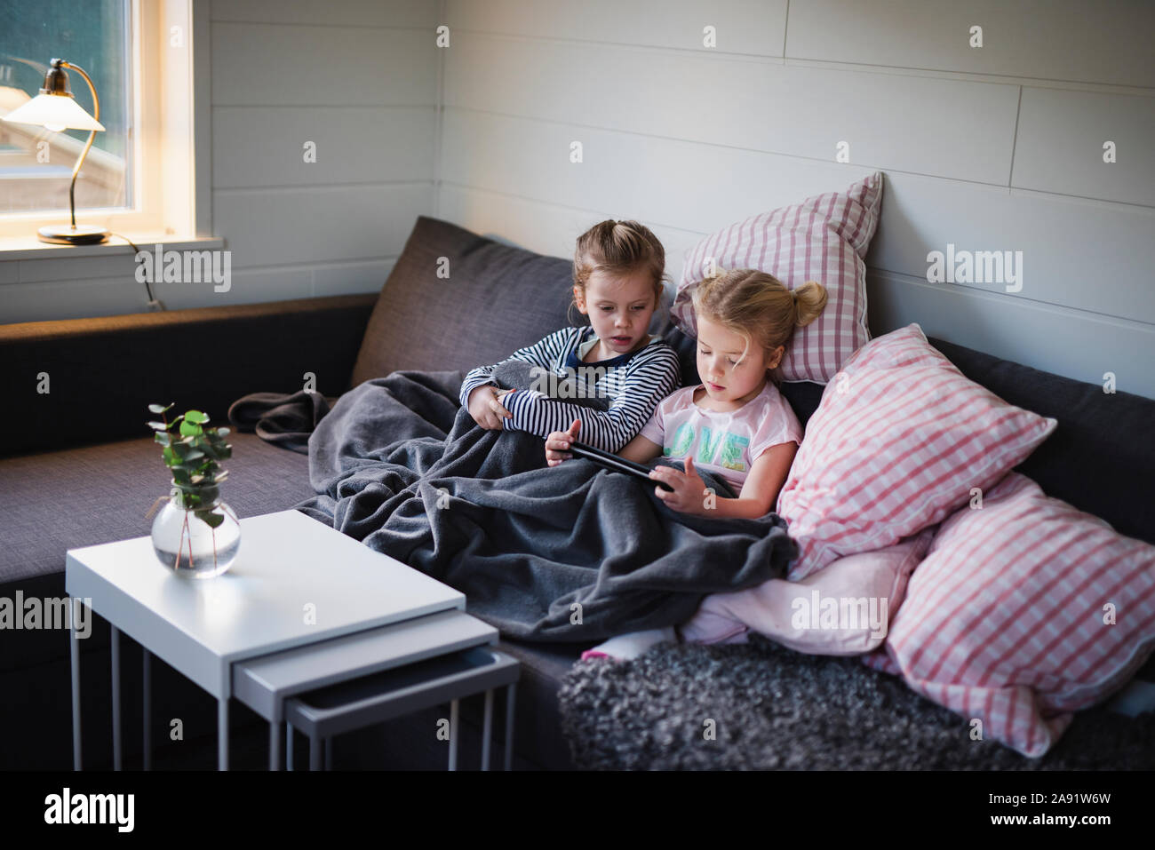 Sorelle seduti sul divano Foto Stock