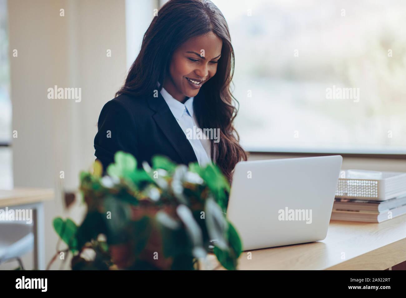 Sorridente giovane americano africano imprenditrice in piedi a un tavolo nella sala di un moderno ufficio a lavorare sul suo computer portatile Foto Stock