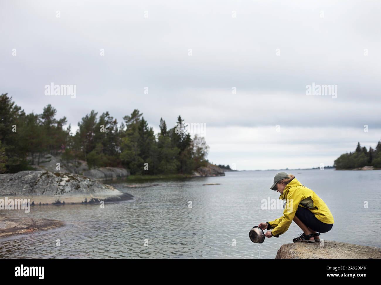 Donna facendo i piatti in un lago Foto Stock