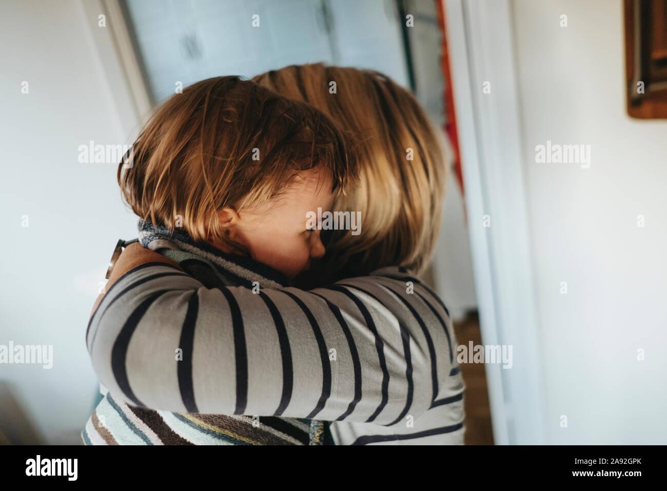 Il Toddler girl avente abbraccio dalla mamma Foto Stock