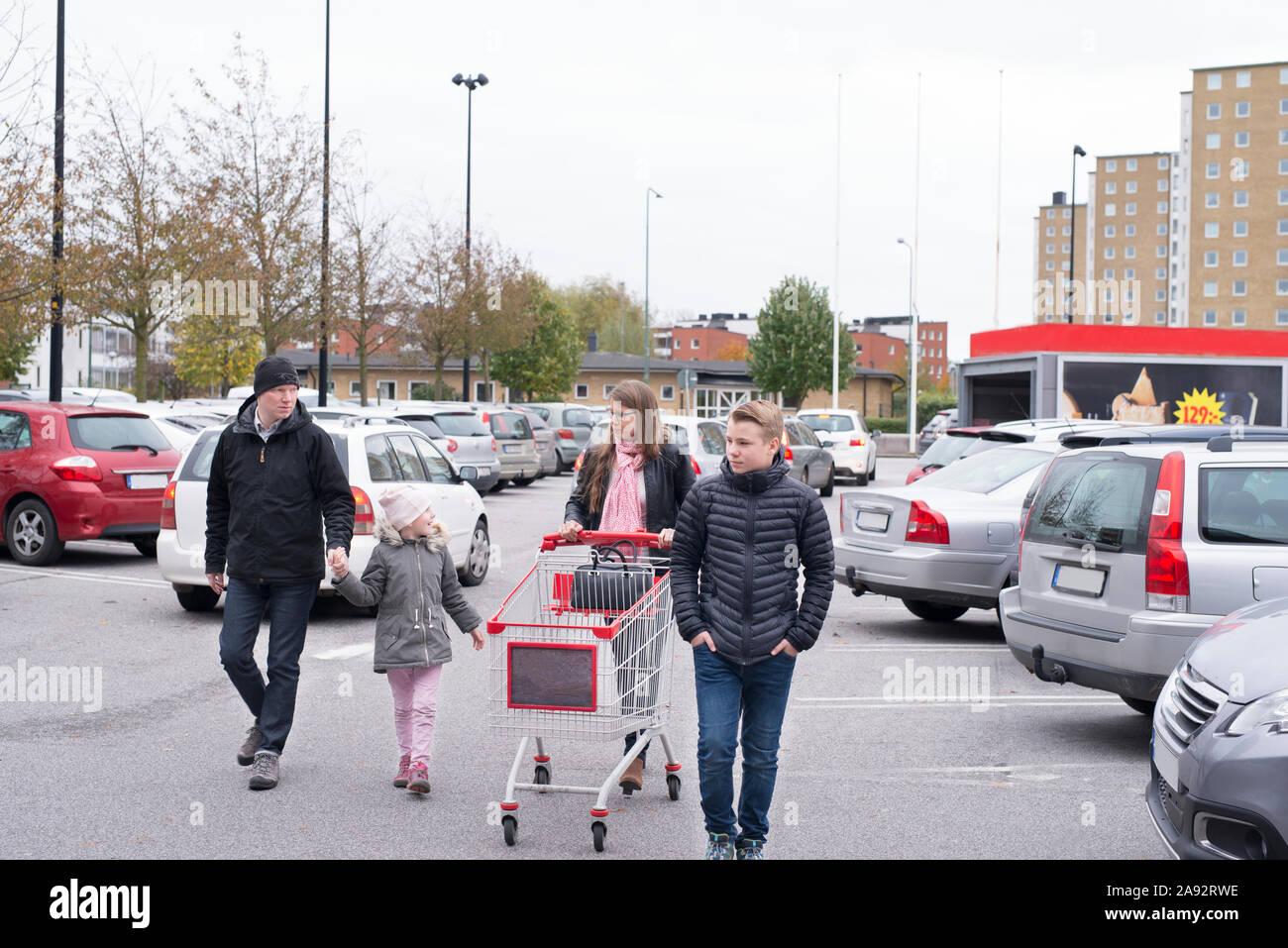 La famiglia sul parcheggio del negozio Foto Stock