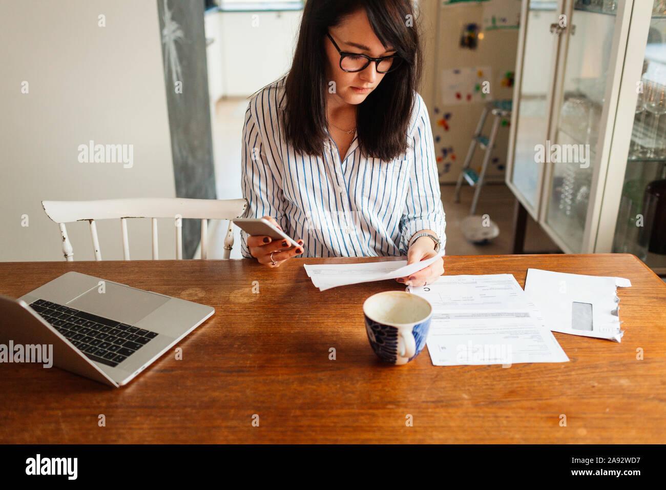 Donna con notebook e smartphone in sala da pranzo Foto Stock