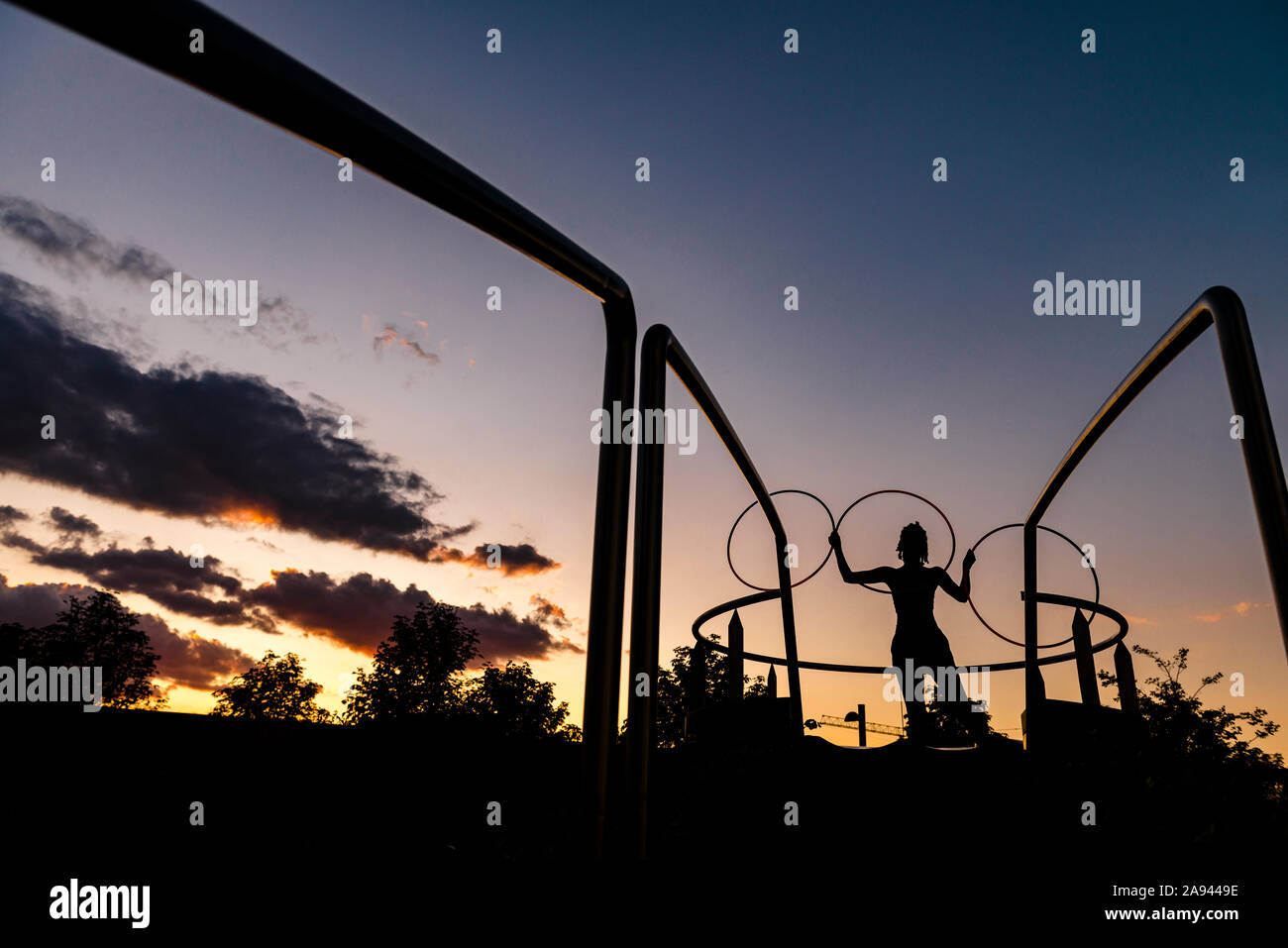 Silhouette di donna eseguendo hula hoop dance in downtown al tramonto Foto Stock